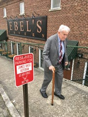 James L. Bass Jr., 97, walks next to one of two parking spots reserved for him near his law office in Carthage, Tenn.