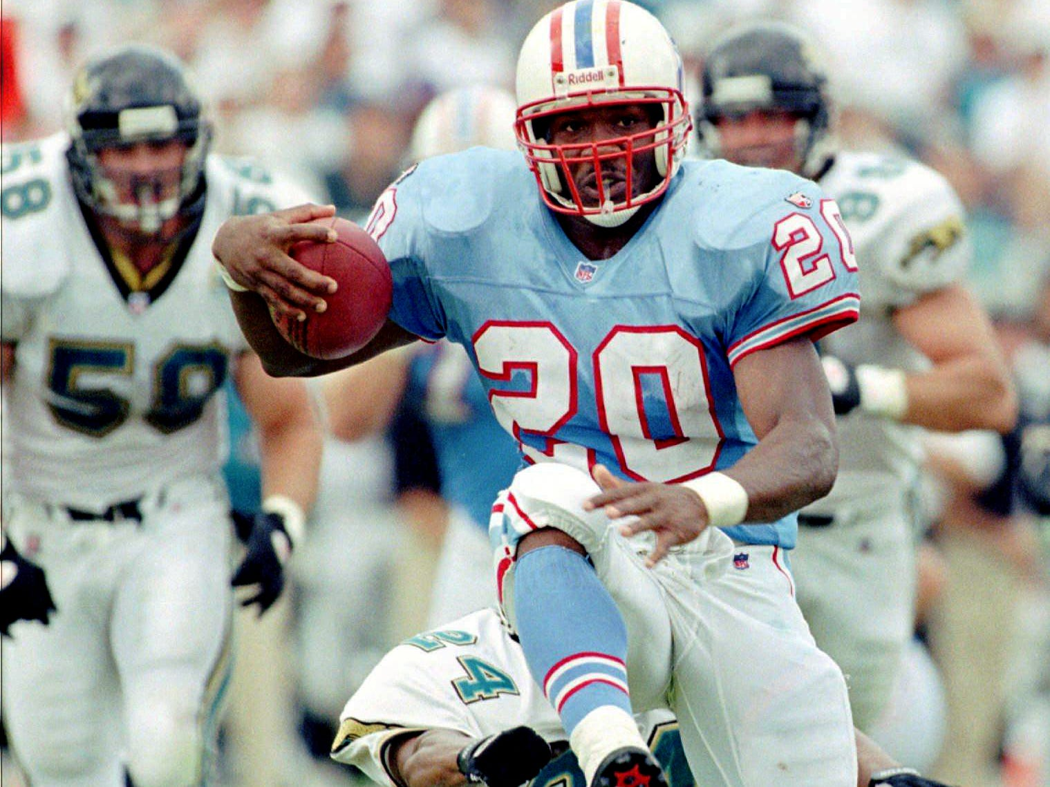 Houston Oilers running back Rodney Thomas (20) high steps away from Jacksonville Jaguars Bryan Schwartz (58) and Harry Colon (24) during a second half run Sept. 3, 1995 in Jacksonville, Fla. The Oilers defeated the Jags 10-3.