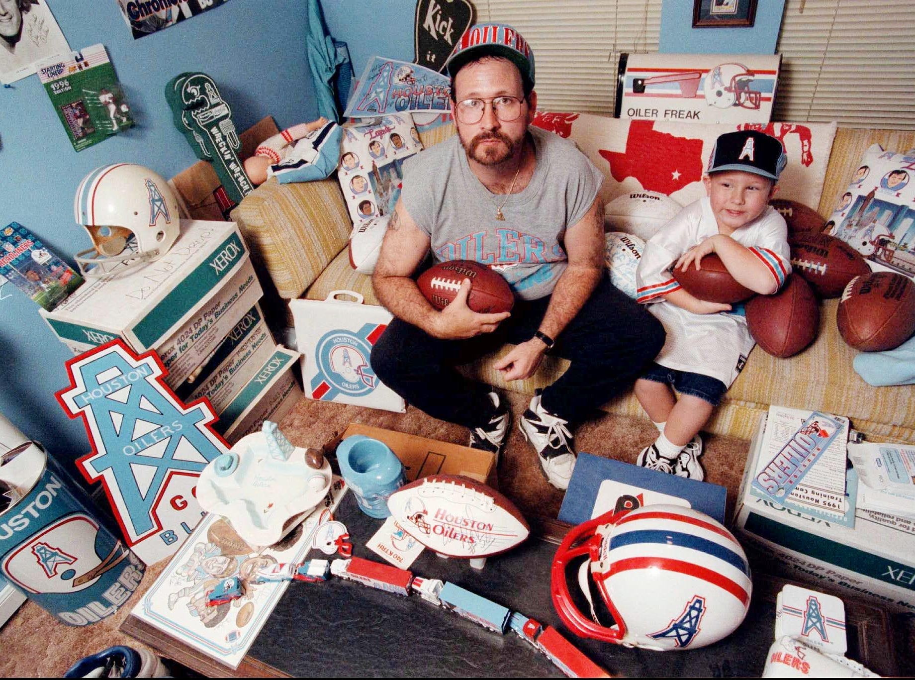 Chris Lockridge, left, holding on to a football used in the last game played by the Houston Oilers in Houston, and his 5-year-old son Derrick, named after the drilling platform logo of the Oilers, sit in the blue room of their Houston home filled with memorabilia dedicated to the former Houston team Dec. 16, 1997. One season has passed since the Oilers moved to Tennessee.