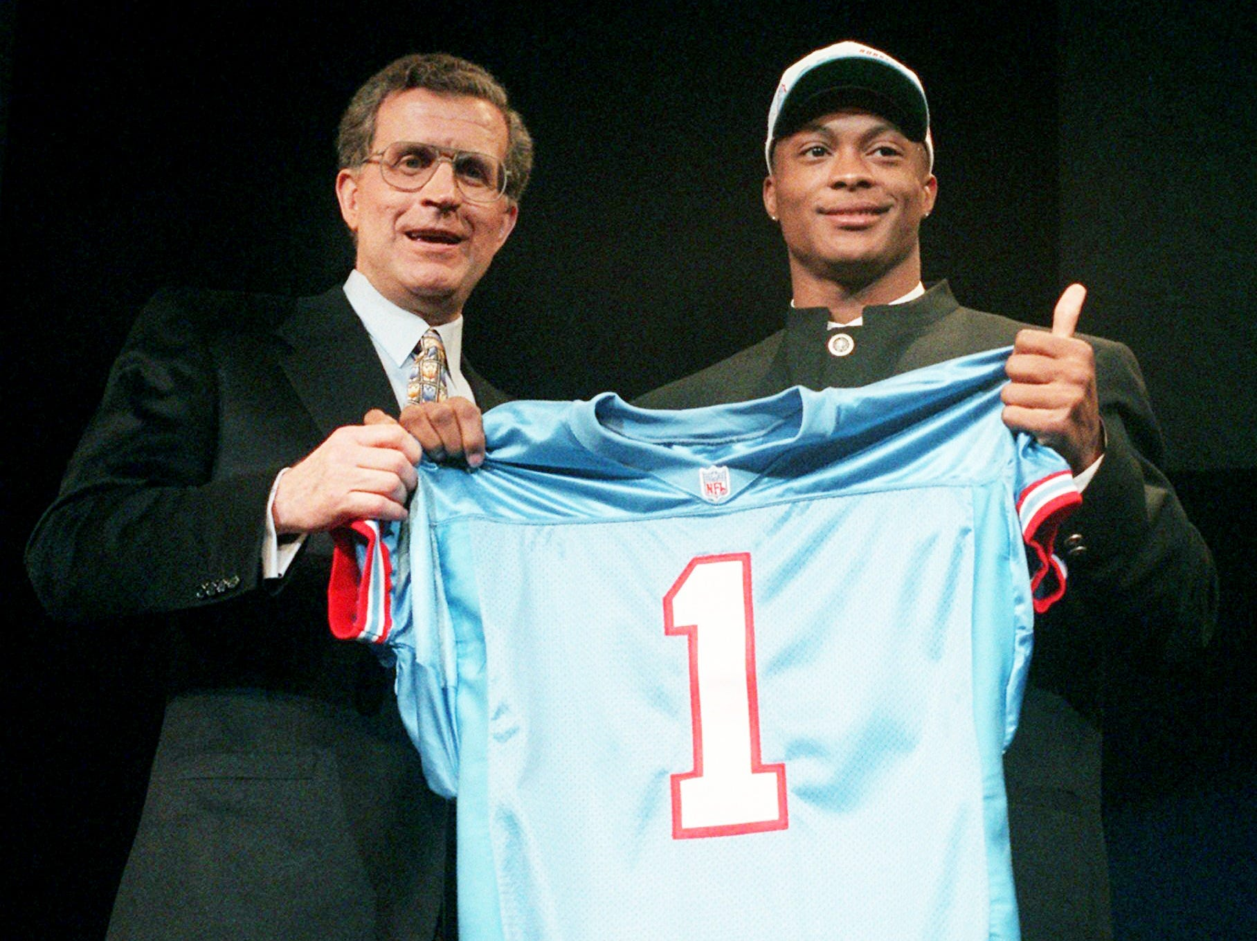 Heisman Trophy-winning running back Eddie George of Ohio State gives a thumbs up while NFL Commissioner Paul Tagliabue, left, helps hold a Houston Oilers football jersey after being taken by Houston as the first round pick in the NFL draft in New York April 20, 1996.
