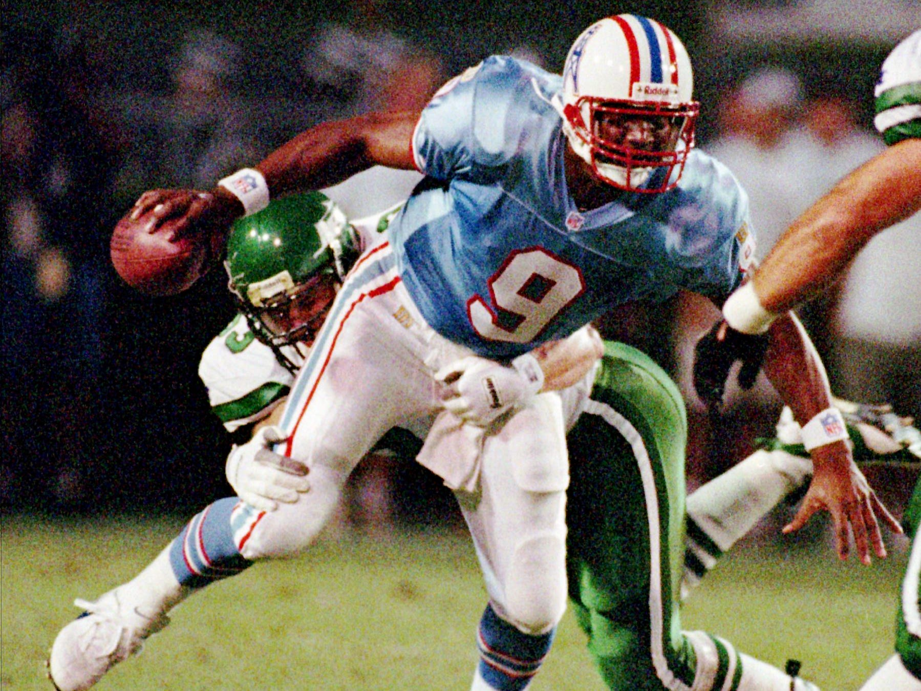 Houston Oilers quarterback Steve McNair attempts to breaks free from a New York Jets defender during a pre-season game in Jackson, Miss. Aug. 3, 1996.