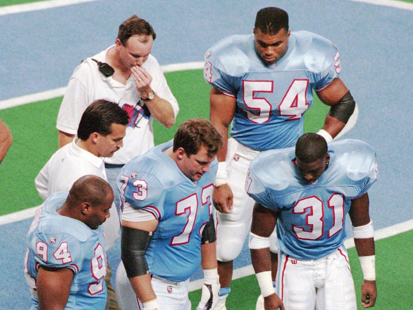 Members of the Houston Oilers look at the Astrodome field before a scheduled game against the San Diego Chargers Aug. 19, 1995 in Houston. The game was canceled after the Astrodome field was deemed to be in unplayable condition from a safety standpoint.