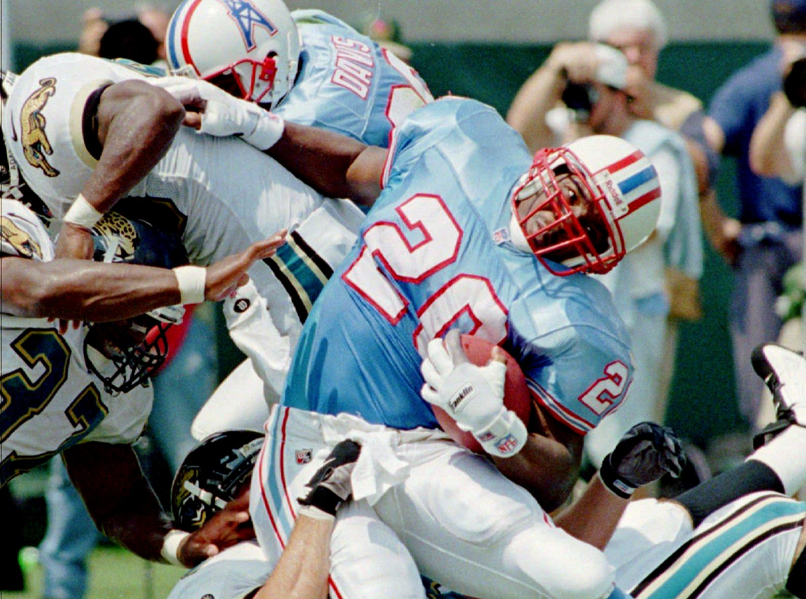 Houston Oilers running back Rodney Thomas (20) is grabbed by Jacksonville Jaguars middle linebacker Bryan Schwartz (58) after picking up six yards during the first quarter of their game Sept. 8, 1996 at Jacksonville Municipal Stadium in Jacksonville.