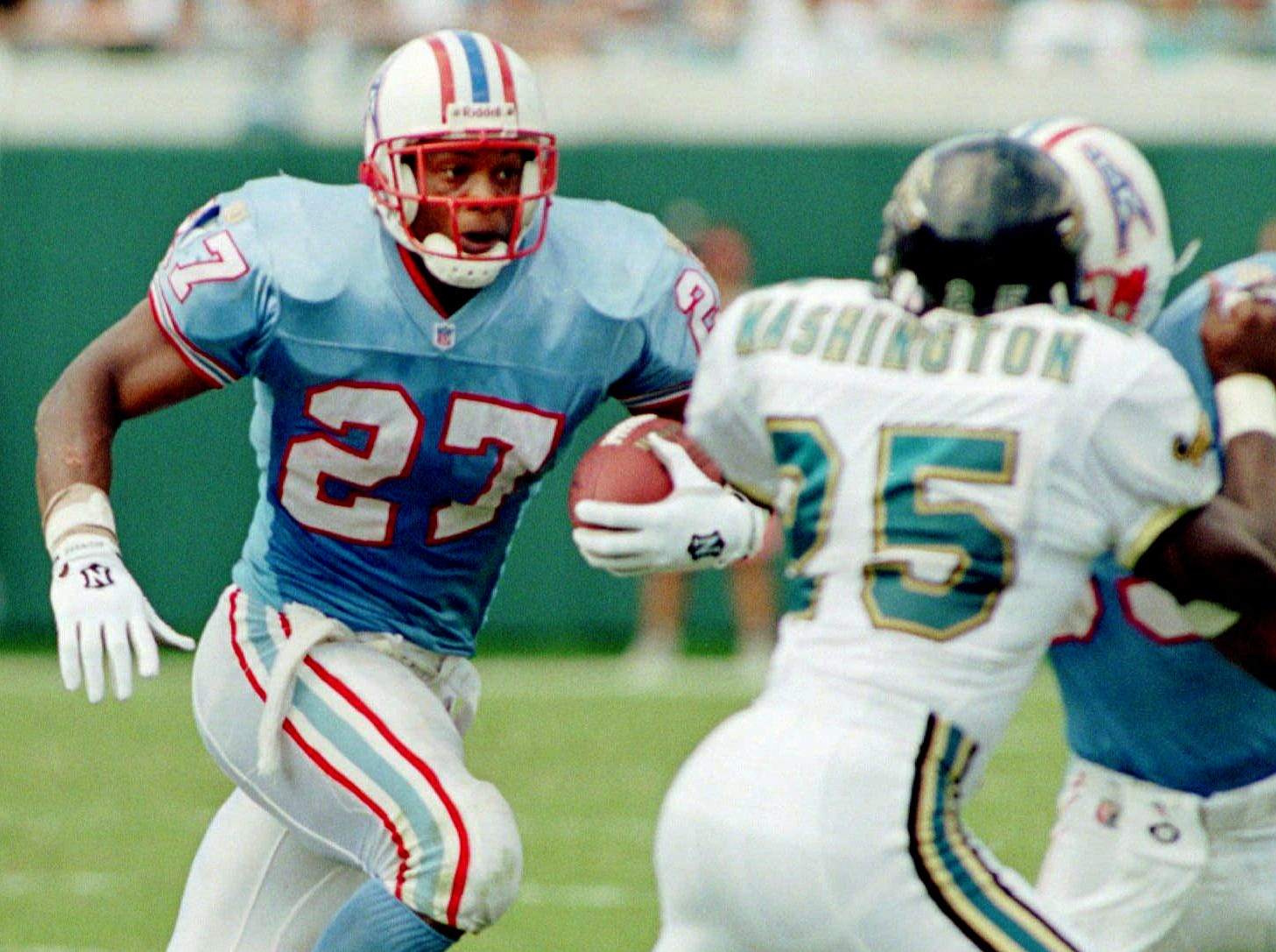 Houston Oilers running back Eddie George (27) follows a block on Jacksonville's Mickey Washington (25) to pick up yardage during their game Sept. 8, 1996 in Jacksonville. George ran for 143 yards on 17 carries in the Oilers 34-17 win.
