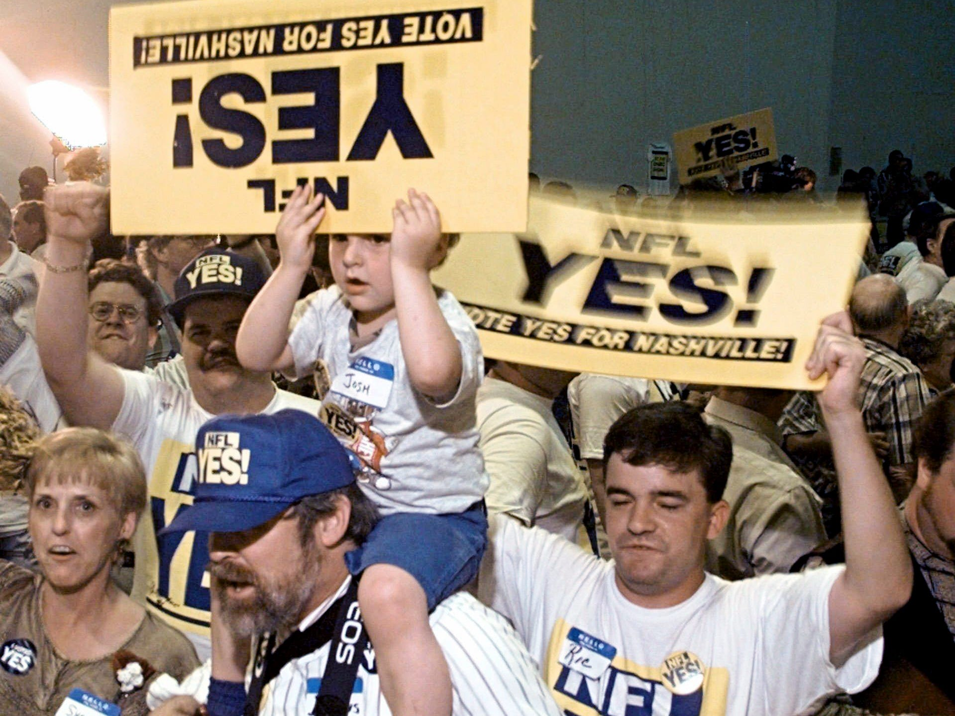 Josh Runkles, 4, holds his sign upside down as he rides on the shoulders of his grandfather, Dennis Schutt, at a victory rally in Nashville May 7, 1996 after voters approved a referendum to bring the Houston Oilers to Nashville in 1998, if not earlier.