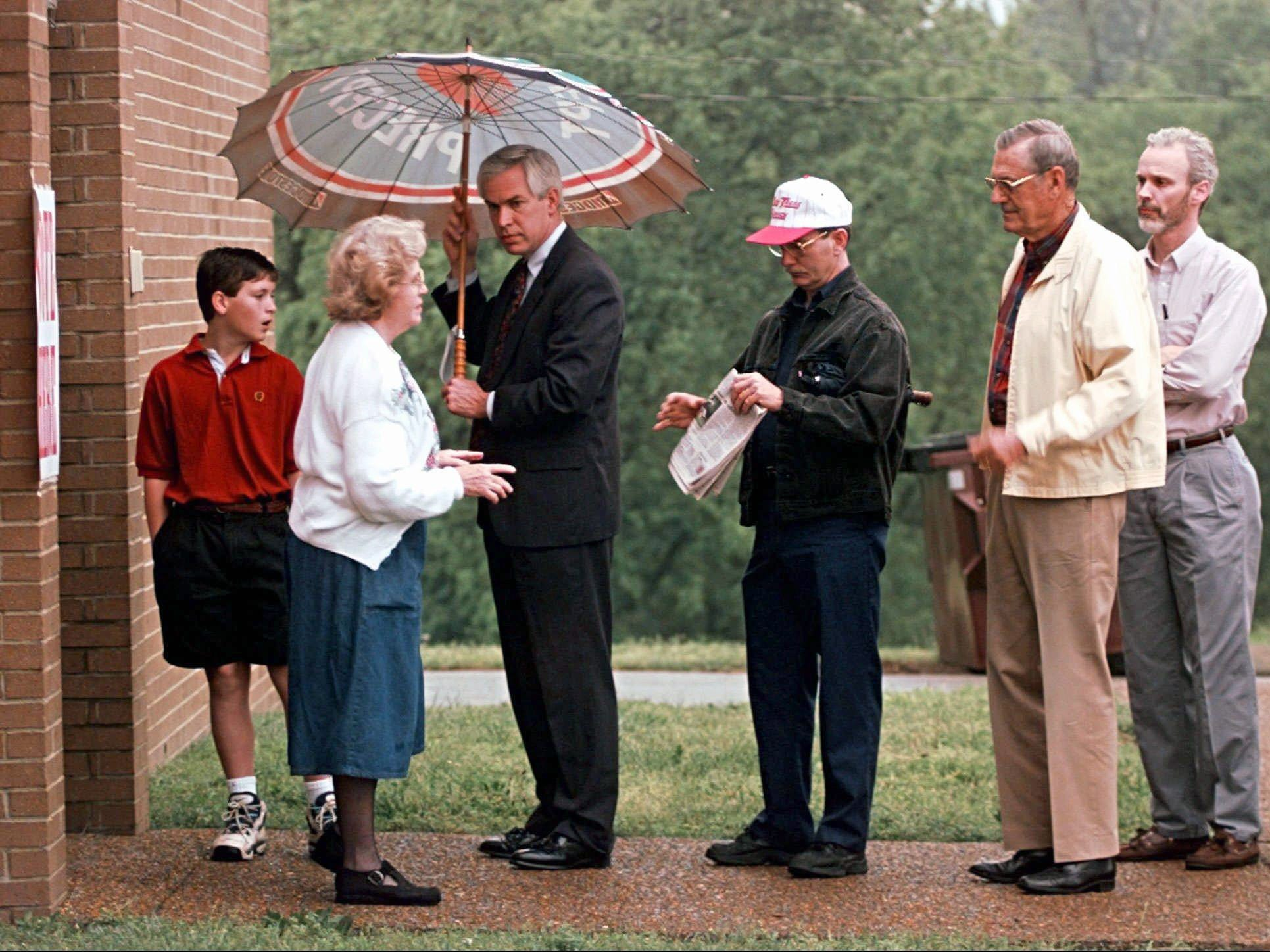Glenda Whitaker, second from left, a poll worker at Holy Trinity Greek Orthodox Church in Nashville, Tenn., tells voters to come in out of the rain as they wait for the doors to open at 7:00 a.m. May 7, 1996. Nashville voters are deciding if public money is going to be used to help build a stadium so the Houston Oilers can move to Nashville.