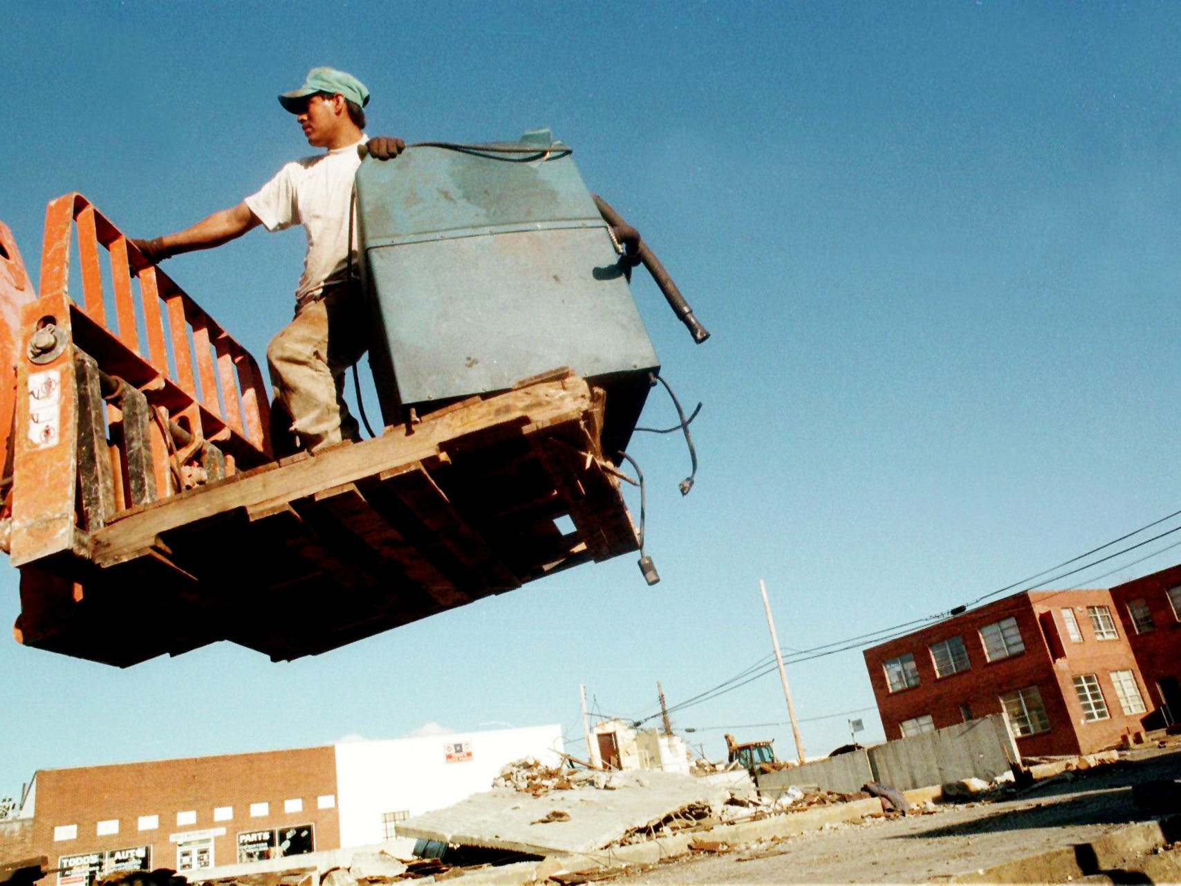 Miguel Taeo with Done Right Contractors of Nashville rides a lift with a piece of machinery being taken from a building formerly used by Enco materials March 7, 1997. The contractors were taking the building down and loading the materials onto a railcar to be transported to Detroit where it will be re-assembled. Enco is the latest business to be moving to make way for the new football stadium.