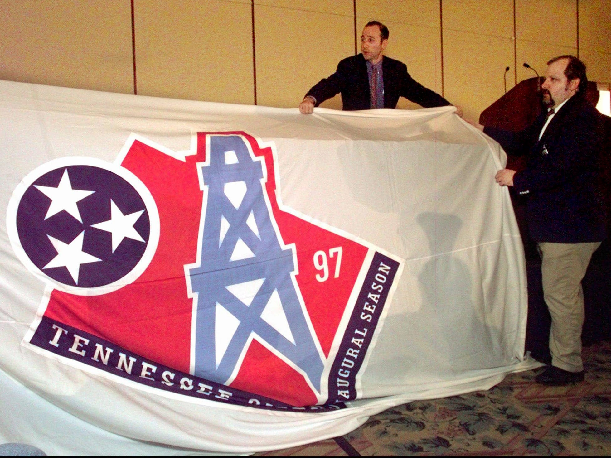 David Goldman, of NFL properties, left, and Alan Reitano drape a banner with the new Tennessee Oilers logo over a table before it is unveiled in Nashville June 12, 1997. The banner was placed over the table after it fell down from the wall. The Oilers will use the new logo during their inaugural season in Tennessee this year.