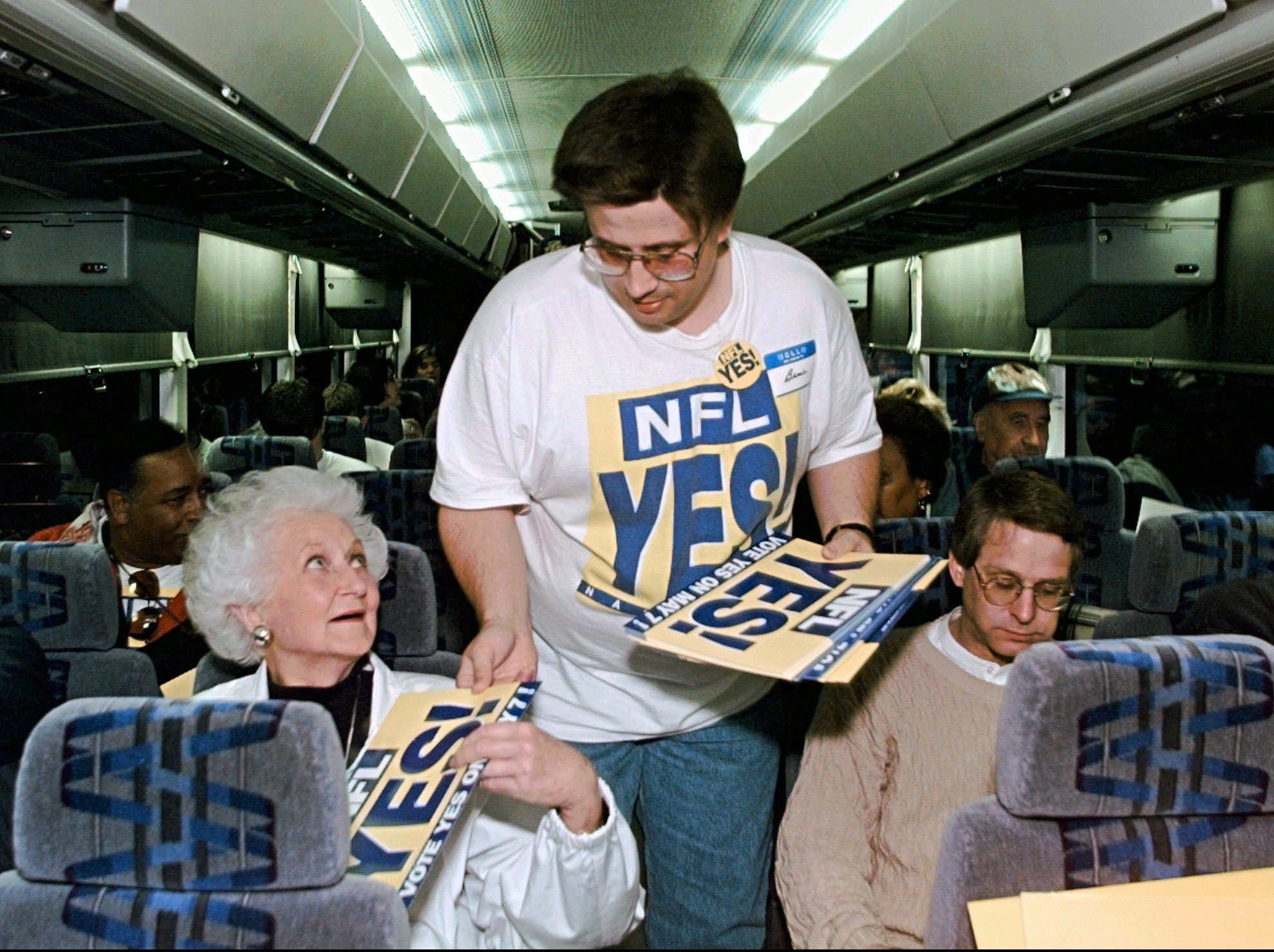 Bruce Odom, center, passes out signs to passengers on a bus preparing to leave Nashville for the NFL owners meeting in Atlanta April 30, 1996. The group is traveling to Atlanta to show support for the Houston Oilers' proposed move to Nashville. The owners are scheduled to vote on the move later in the day.