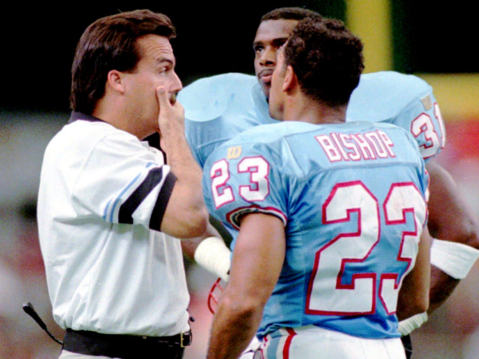 Houston Oilers coach Jeff Fisher, left, talks to Marcus Robertson, center, and Blaine Bishop on the sidelines during the game Sept. 1, 1996 in Houston. The Oilers lost 20-19 to the Kansas City Chiefs.