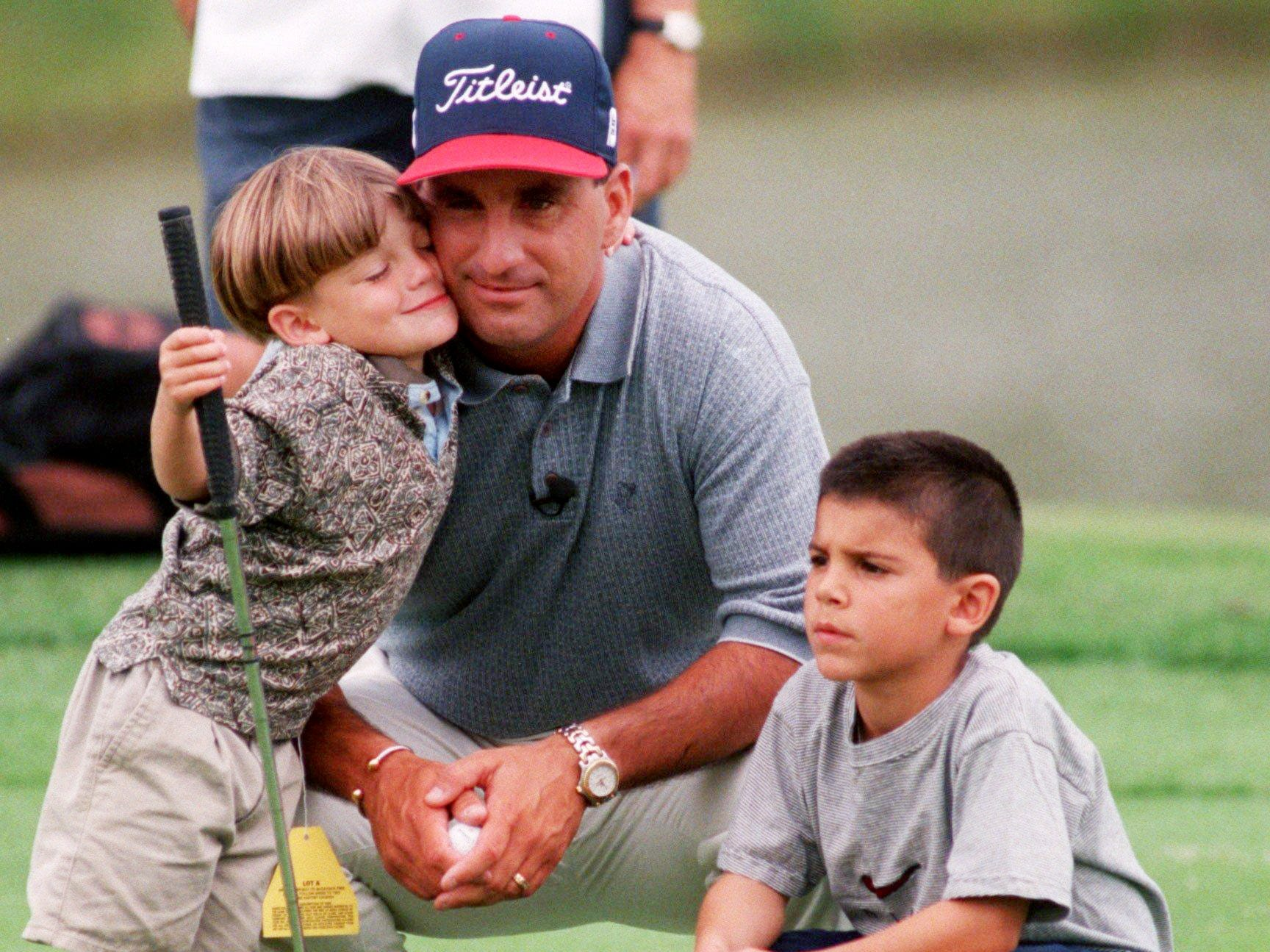 Kicker Al Del Greco of the Houston Oilers with sons Derrick 3-years-old and Trey 7-years-old, are on the 18th green of the Gary Chapman Celebrity Shoot-Out at the Bellsouth Senior Classic June 3, 1997 in Nashville. The Oiler gets a hug from son Derrick while the three were waiting for their turn to put.