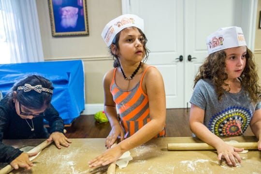 From left, Gabriella Chernysh, Chelsea Guttman and Tori Fuchs, all age 8 then, make Matzah during the Traveling Passover Matzah Bakery workshop at the Chabad Jewish Center of Naples in March 2017.