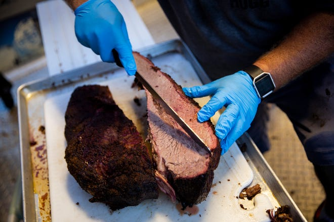 Aric Tousignant slices a brisket at the Nawty Hogg Backyard BBQ food truck in November 2018 at Celebration Park in East Naples. Nawty Hogg's brick-and-mortar restaurant is targeted to open this month on the southwest corner of Collier Boulevard and Pine Ridge Road.