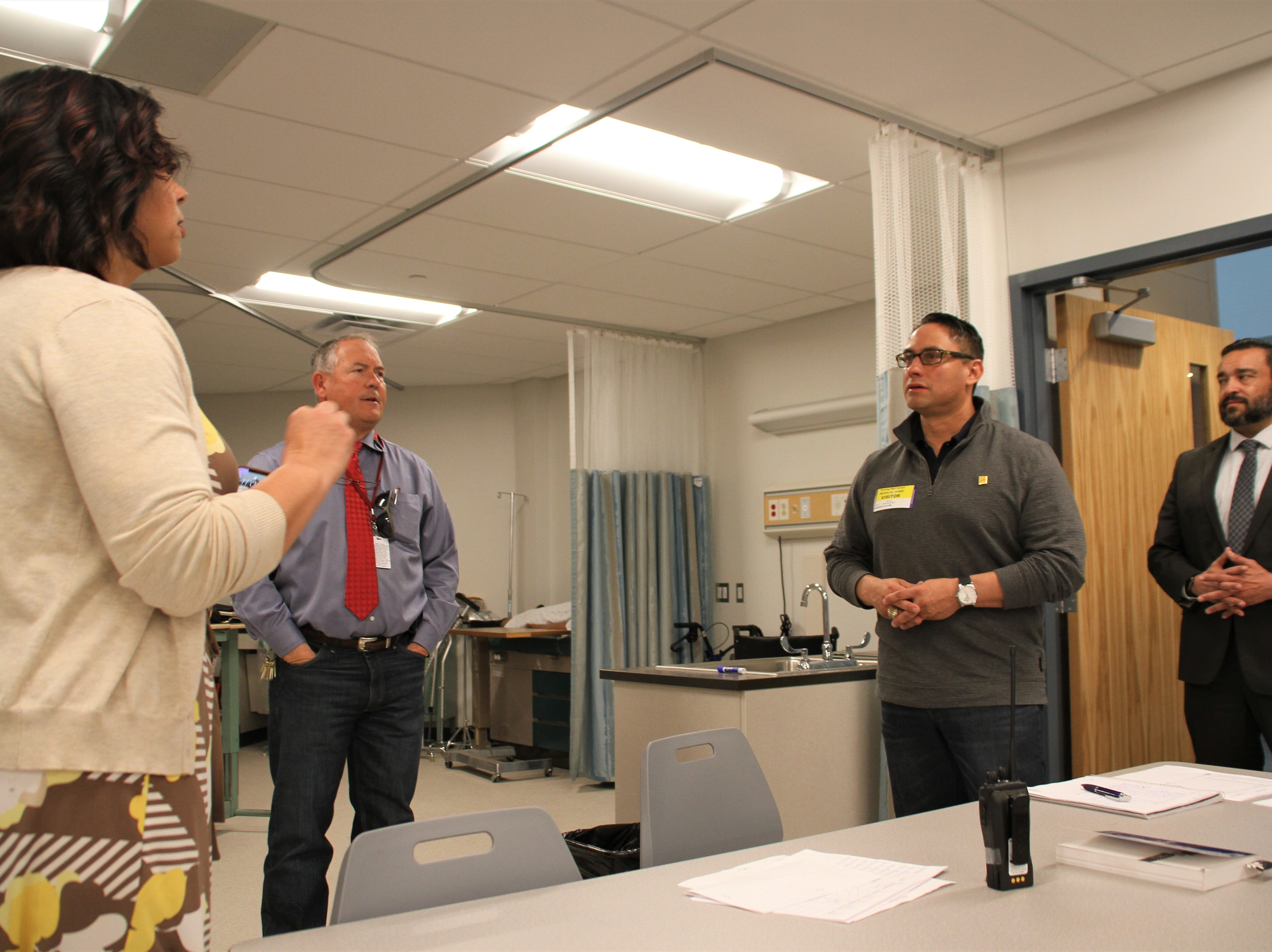 Howie and the group of administrators inside a health occupations classroom.