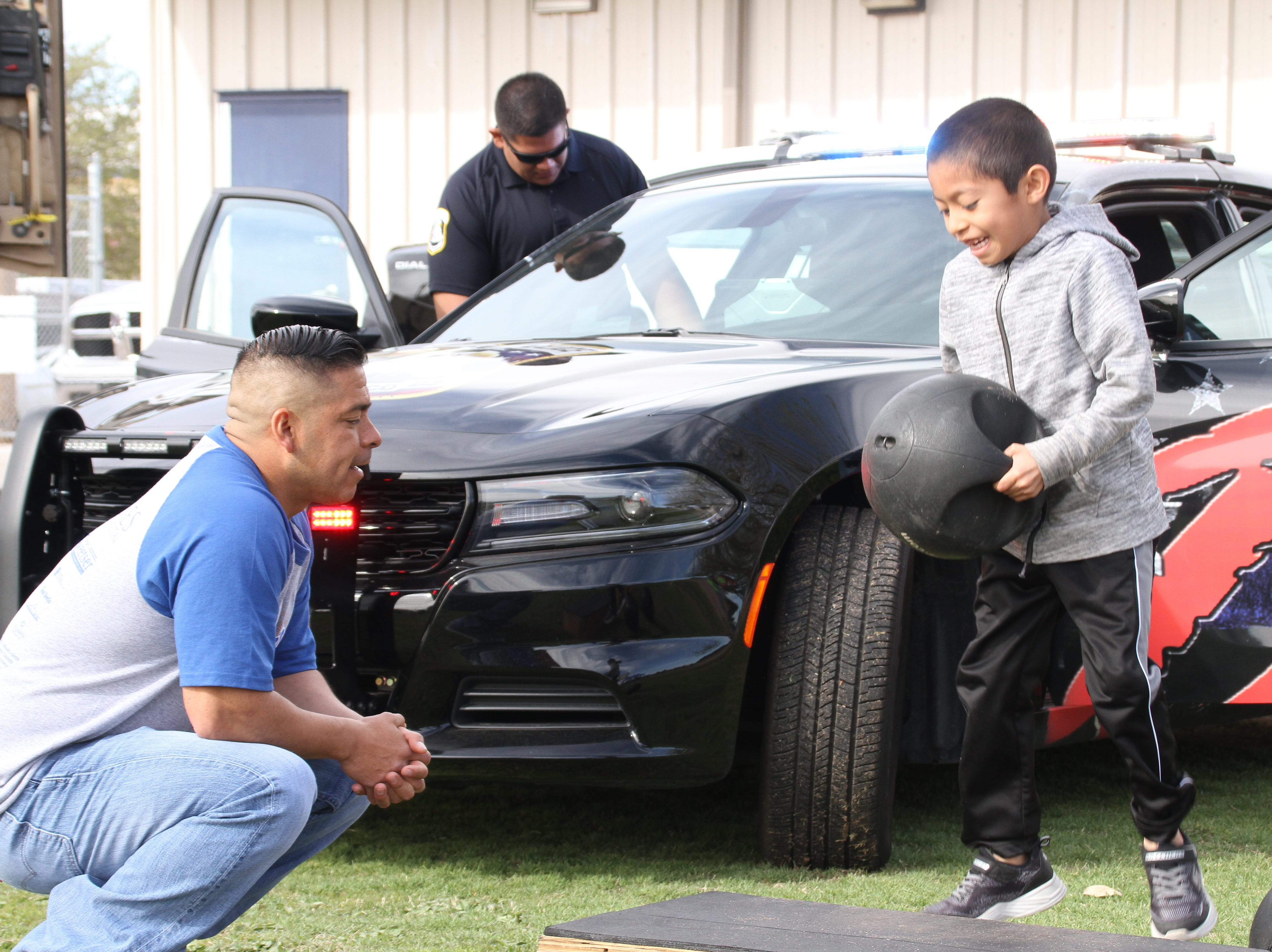 Deming Police hosts an obstacle training course for the kids during the second annual Deming Autism Walk. From left, police officer Nick Perez watches over 6-year-old Aleks Rodriguez complete the course.