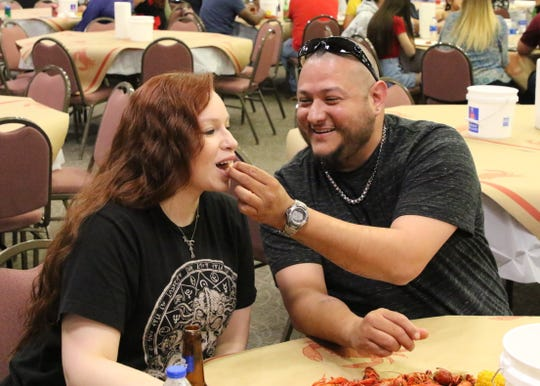 Ricky Almanza feeds Britni Jacquez her first ever taste of a crawfish boil dinner during Monday's NCAA Championship game at the Pecos River Village Conference Center.