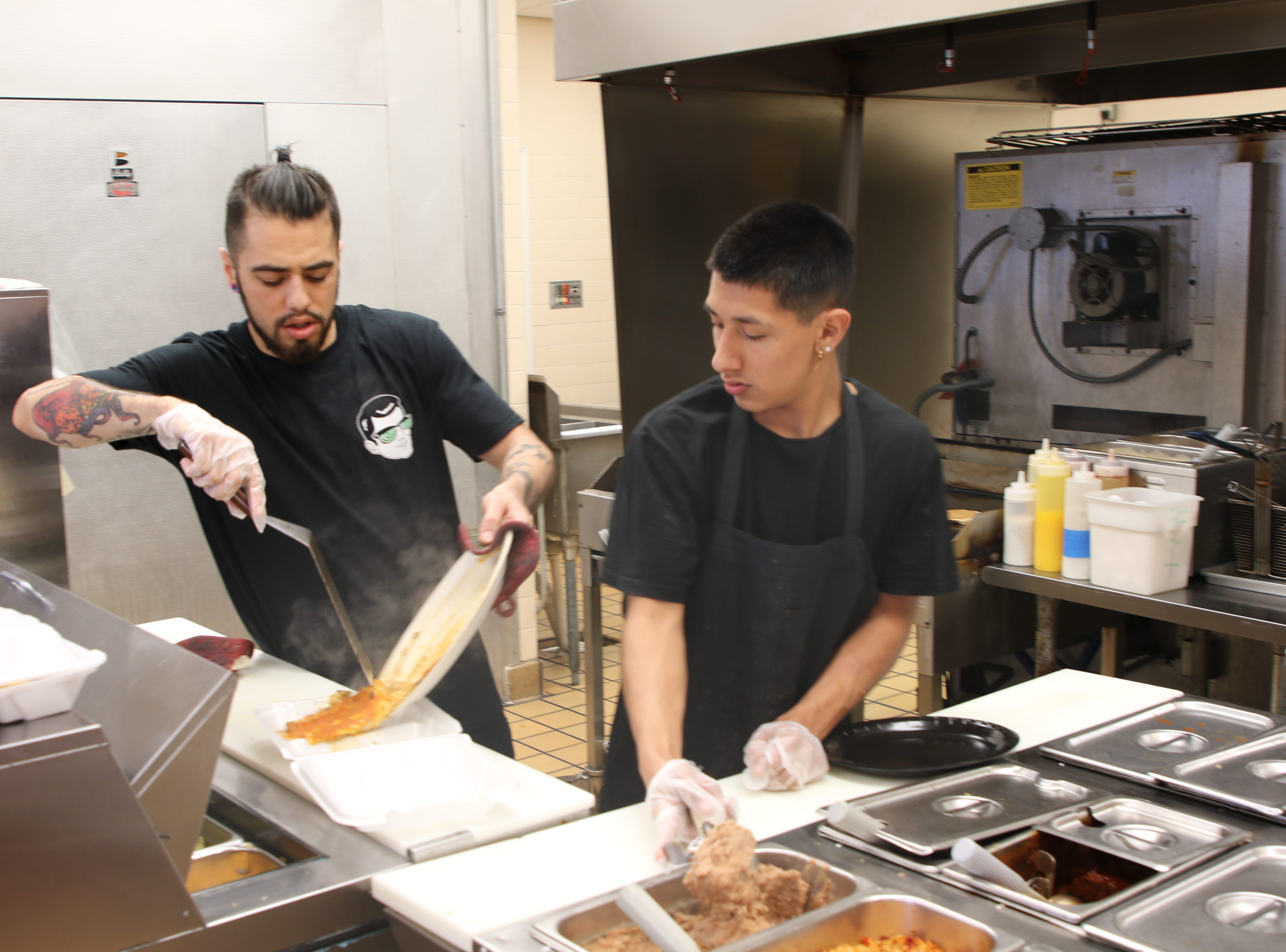 Gabriel Smith (left) and Julian Moreno prepare a meal at PJ and B's Rio Cafe in Carlsbad.