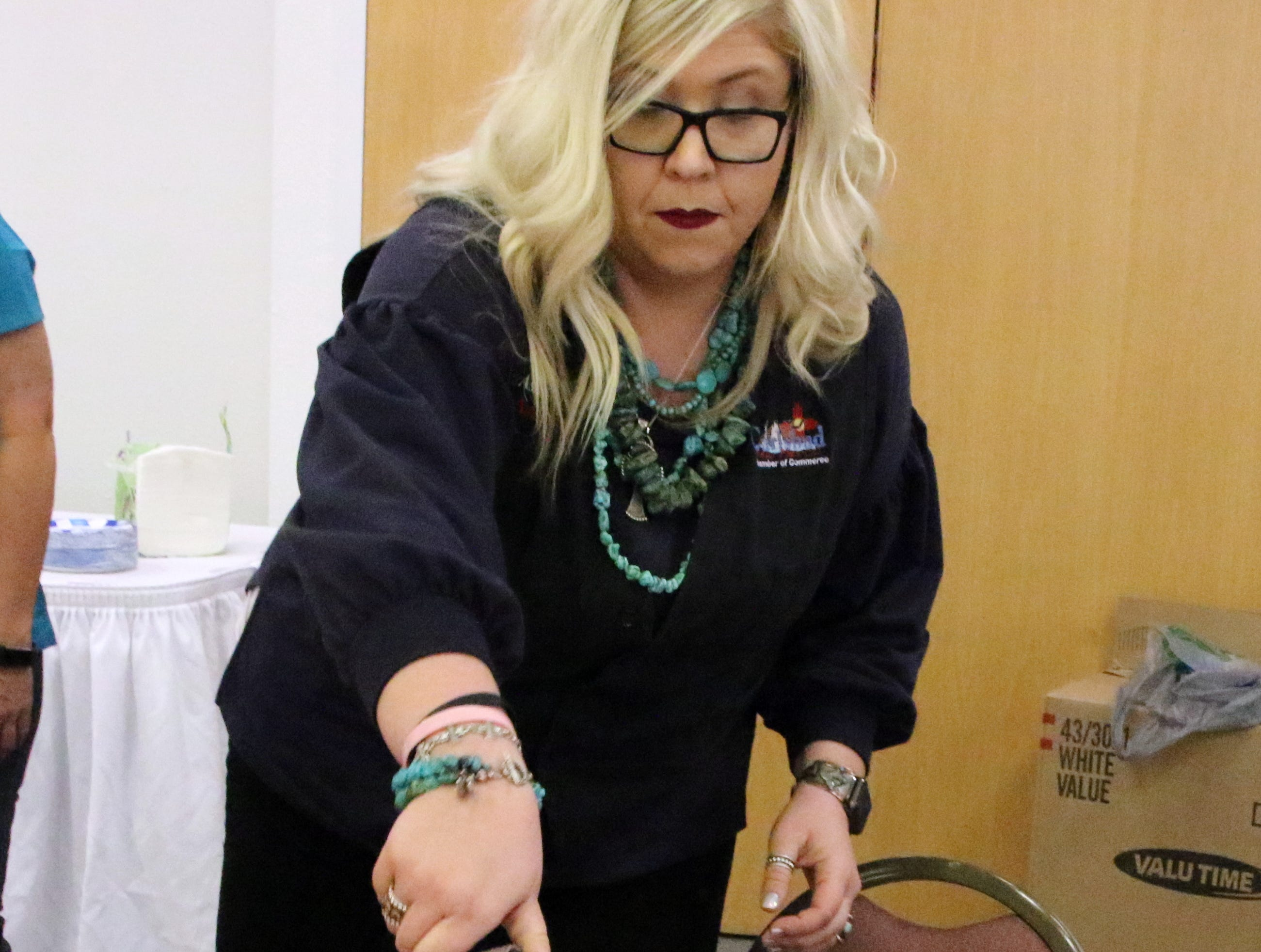 Ashley Switzer pours out a serving of the crawfish boil dinner during Monday's NCAA Championship game at the Pecos River Village Conference Center.