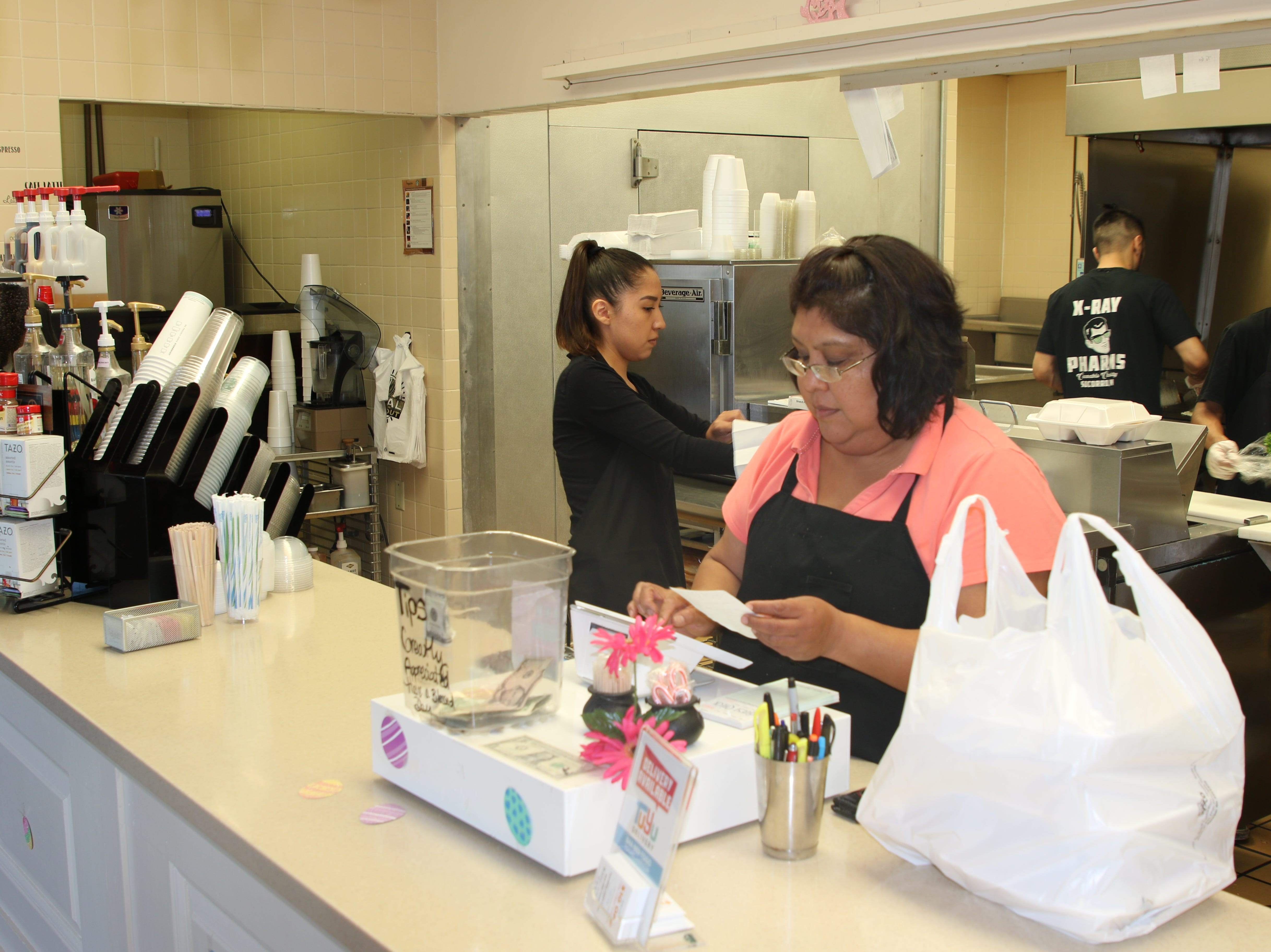 Brittany Tsosie (left) and Charlene Waddoups work behind the counter at PJ and B's Rio Cafe in Carlsbad.