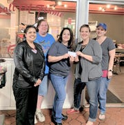 Vice President of the Warrior Pride Booster Club Michelle Otero, Board Member Cynthia Powers, Hall of Flame owner Cyndi Espinoza, and board member Sarah Wilson (from left to right) during the presentation of $2,220 that was raised during a month long raffle.