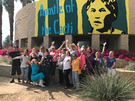 "Artist Olek, kneeling, celebrates the unveiling of a mural of yarn that hangs in front of Palm Desert City Hall with many of the volunteers who helped crochet the art piece, on Saturday, April 6, 2019. The mural is part of Olek's ""Love Across the USA"" project."
