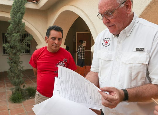 Asylum seeker Alexo Cardenas, left, and Father Guy Wilson look over Cardenas' immigration paperwork at Our Lady of Soledad Church in Coachella, April 8, 2019.