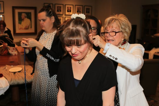 Angel View Fashion Show committee member Ursula Gari helps client and model Marlina prepare for the runway.