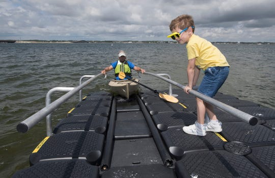 Five-year-old Kelvin Hall helps Dave Barker put his kayak into the water Tuesday at the newly renovated Navarre Beach Marine Park. Santa Rosa County officials unveiled the improved ADA-friendly park to the public during a ceremony earlier in the day.