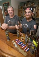 Paul and Patrick Rollins, the owners of Rollins Distillery in Gulf Breeze, show off their award-winning spirits on Tuesday.