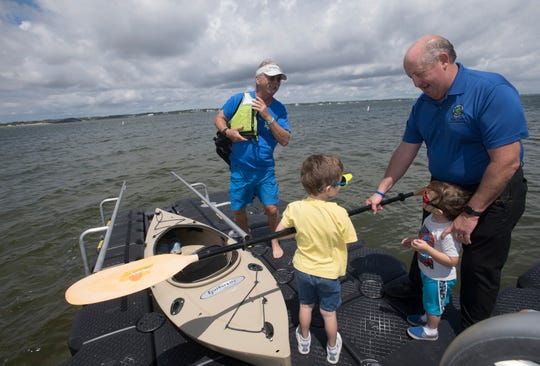 Santa Rosa County Commissioner Dave Piech helps Kelvin and Kyle Hall as the two youngsters help out Dave Barker, who is putting his kayak into the water at the Navarre Beach Marine Park on Tuesday.