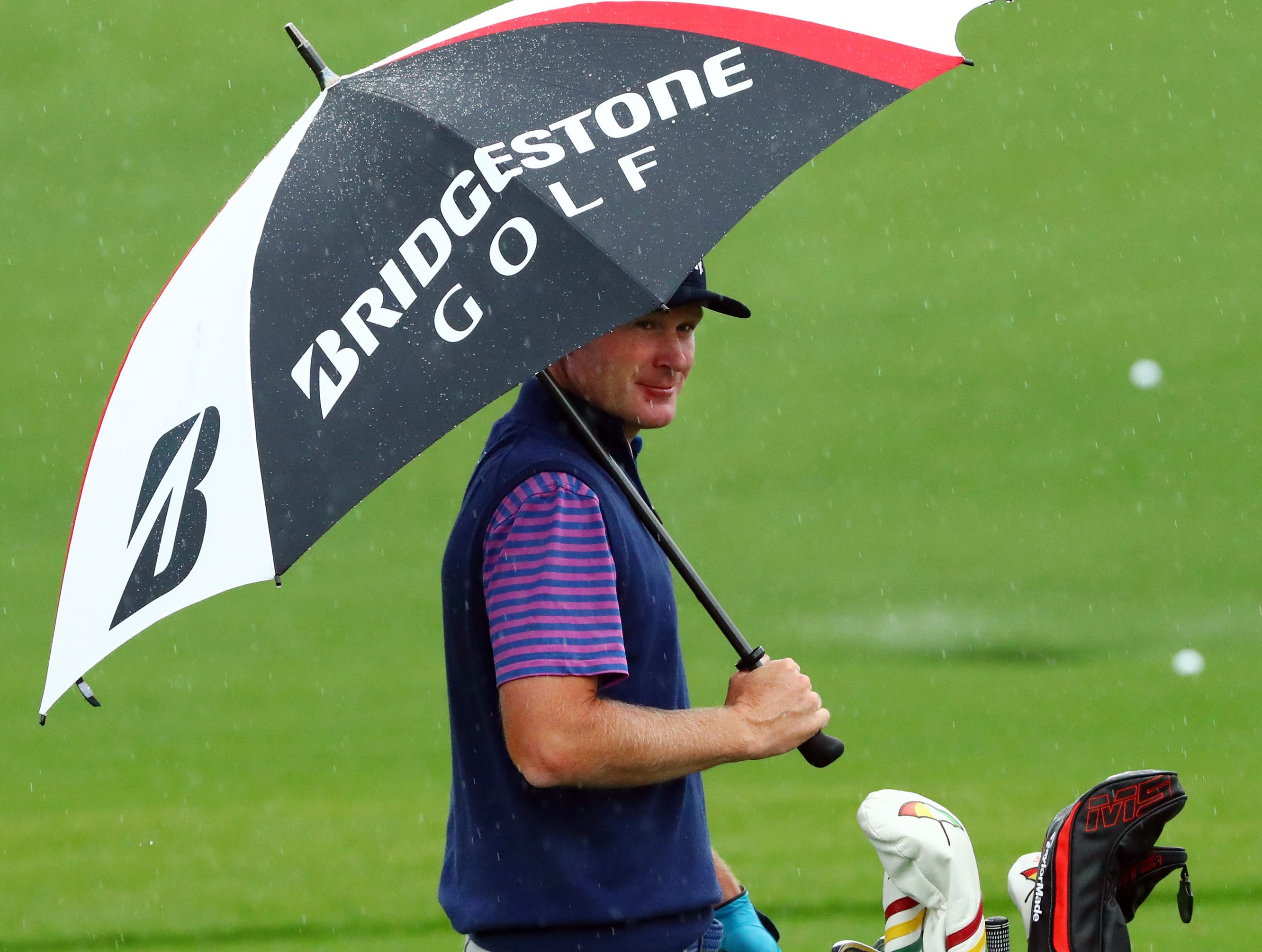 Apr 9, 2019; Augusta, GA, USA; Brandt Snedeker protects himself from the rain at the practice facility during a practice round for The Masters golf tournament at Augusta National Golf Club. Mandatory Credit: Rob Schumacher-USA TODAY Sports