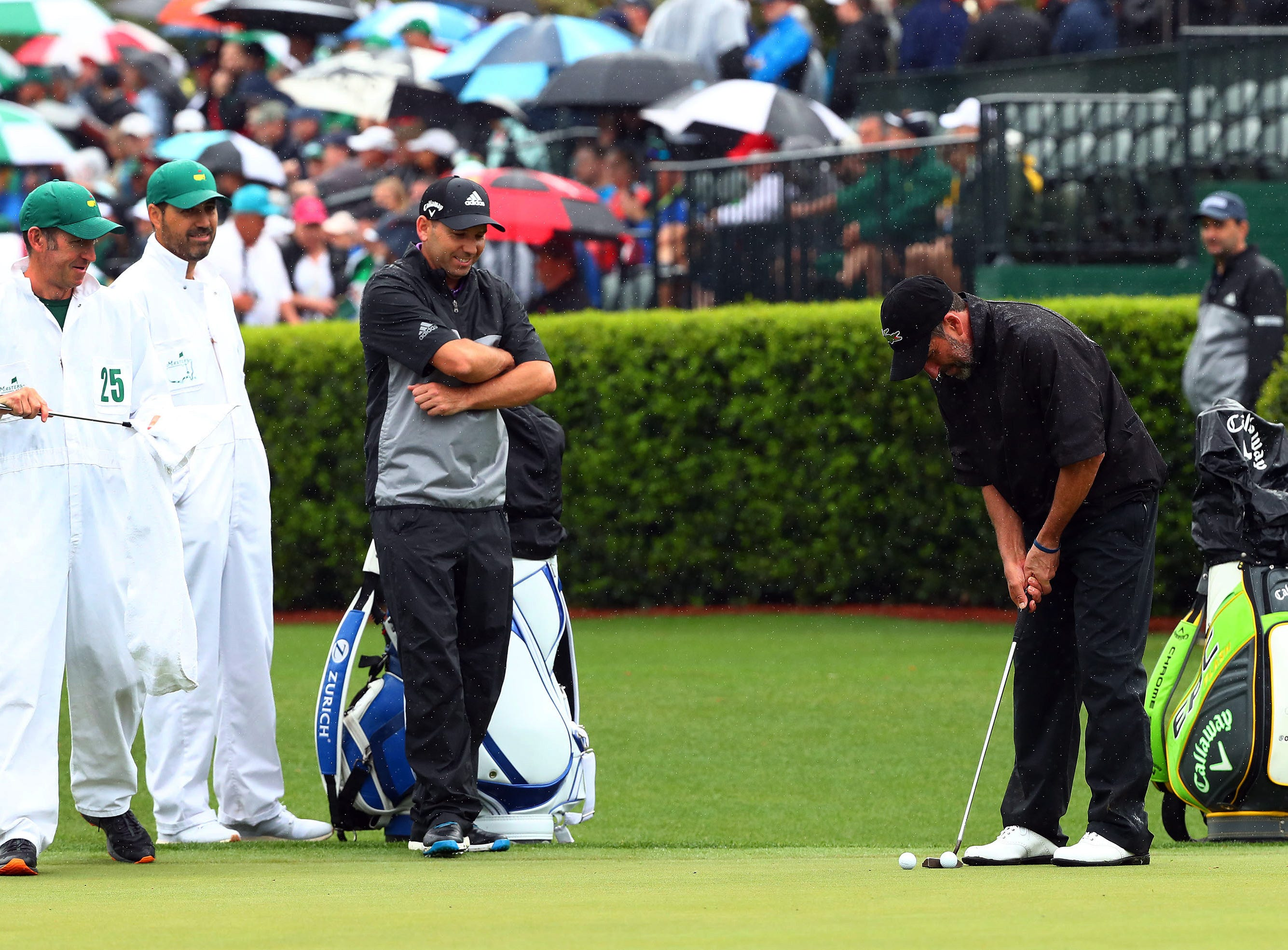 Apr 9, 2019; Augusta, GA, USA; Sergio Garcia of Spain watches Jose Maria Olazabal of Spain putt at the practice facility during a practice round for The Masters golf tournament at Augusta National Golf Club. Mandatory Credit: Rob Schumacher-USA TODAY Sports