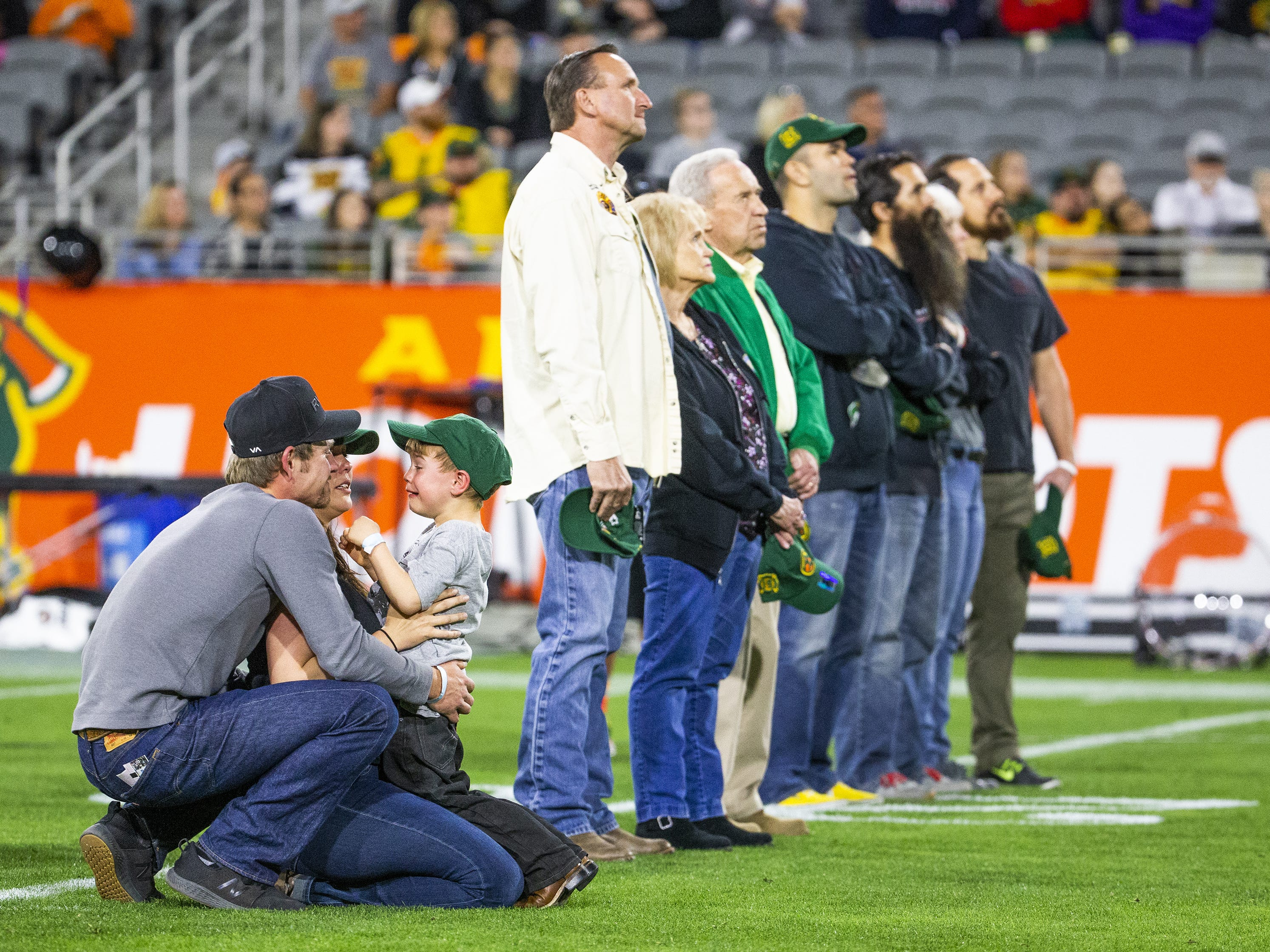 Amanda Misner-Parker holds her son, Jaxon Misner, 6, whose father was Granite Mountain Hotshot Sean Misner, as Jaxon cries during a tribute on the jumbotron to the fallen firefighters.  The tribute, at halftime of the Arizona Hotshots and Atlanta Legends football game at Sun Devil Stadium, Sunday, March 3, 2019, included a giant banner being unfurled, retiring the number 19 in honor of the fallen firefighters. At left is D.J. Parker, brother of Wade Parker, one of the Granite Mountain Hotshots who is now Amanda's husband.
