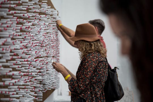 """The Last Word"" by Illegal Art features hundreds of tightly rolled pieces of paper where participants can read and write things that have never been said."