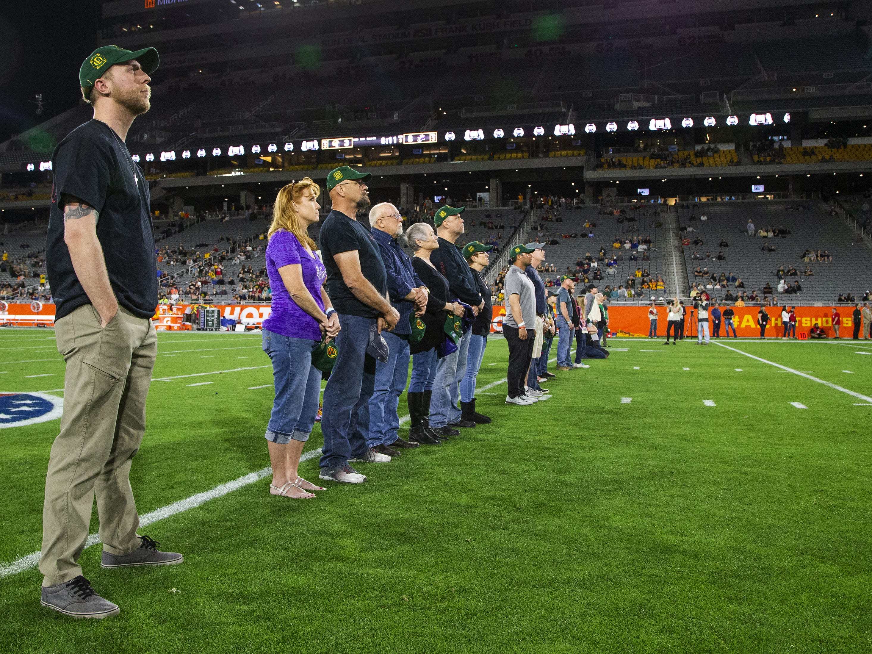 Brendan McDonough, the lone-surviving member of the Granite Mountain Hotshots, left, and family members of the crew,  watch a tribute on the jumbotron while being honored at halftime of the Arizona Hotshots and Atlanta Legends football game at Sun Devil Stadium, Sunday, March 3, 2019.  A giant banner was unfurled, retiring the number 19 in honor of the fallen firefighters.