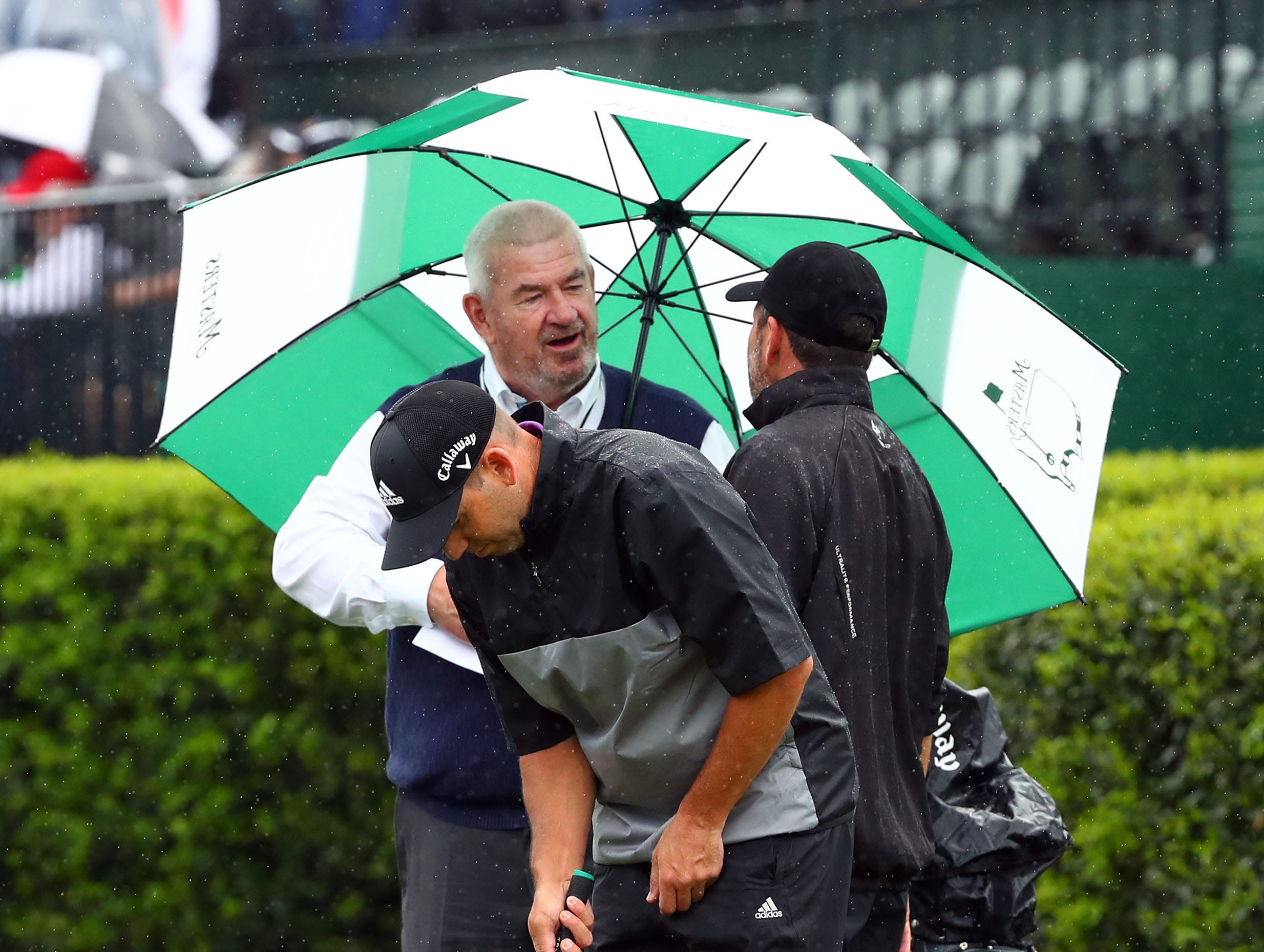 Apr 9, 2019; Augusta, GA, USA; Jose Maria Olazabal of Spain talks with John Paramor, the European Tour's chief rules official, as Sergio Garcia of Spain (front) putts at the practice facility during a practice round for The Masters golf tournament at Augusta National Golf Club. Mandatory Credit: Rob Schumacher-USA TODAY Sports