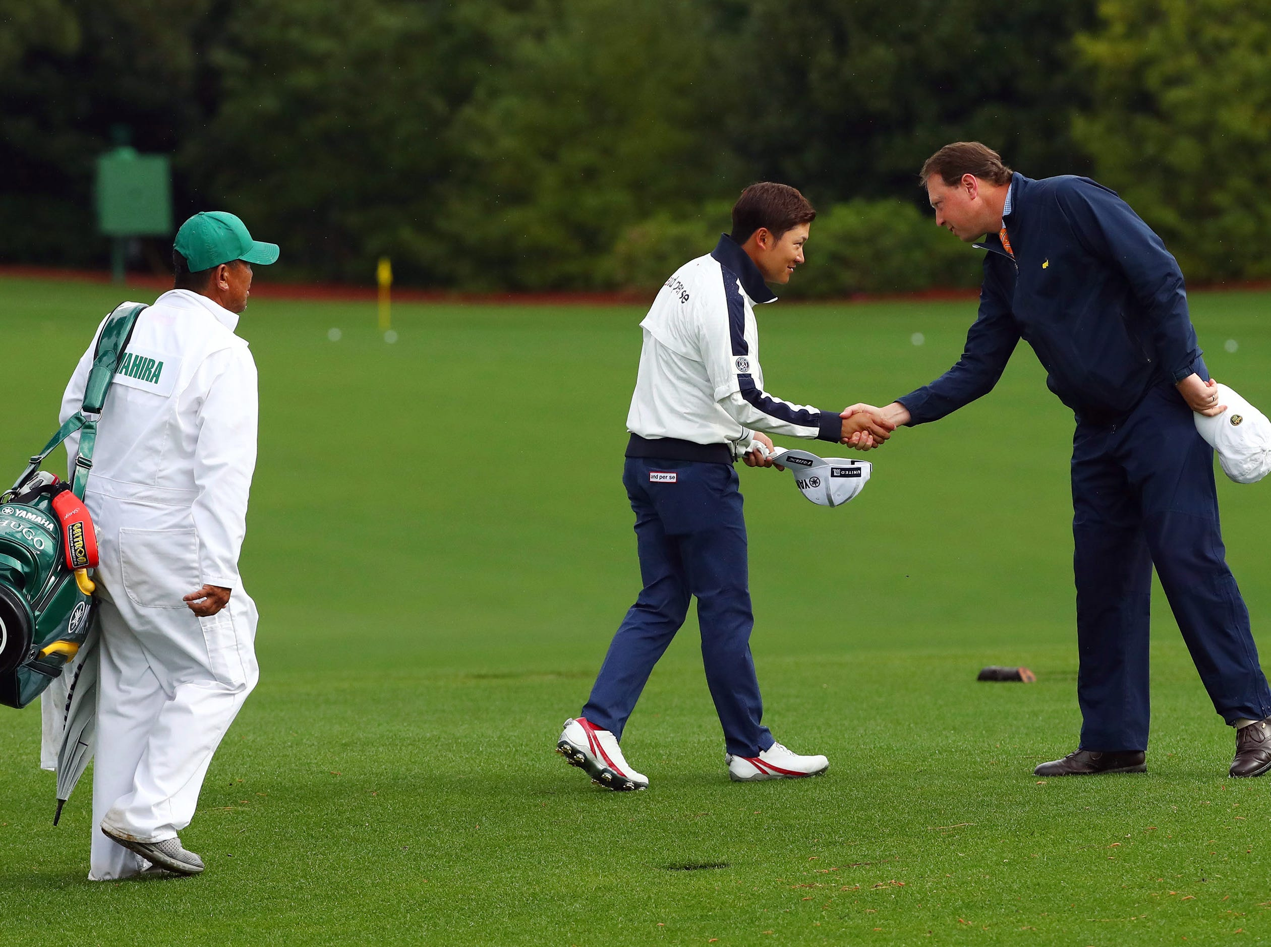 Apr 9, 2019; Augusta, GA, USA; Shugo Imahira of Japan (center) is greeted at the practice facility during a practice round for The Masters golf tournament at Augusta National Golf Club. Mandatory Credit: Rob Schumacher-USA TODAY Sports