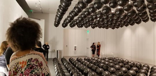 """Black Balloons"" by Tadao Cern is comprised of balloons with opposing weights. The artwork is part of Wonderspaces Arizona, an immersive art show open April through mid-July 2019 at Scottsdale Fashion Square."