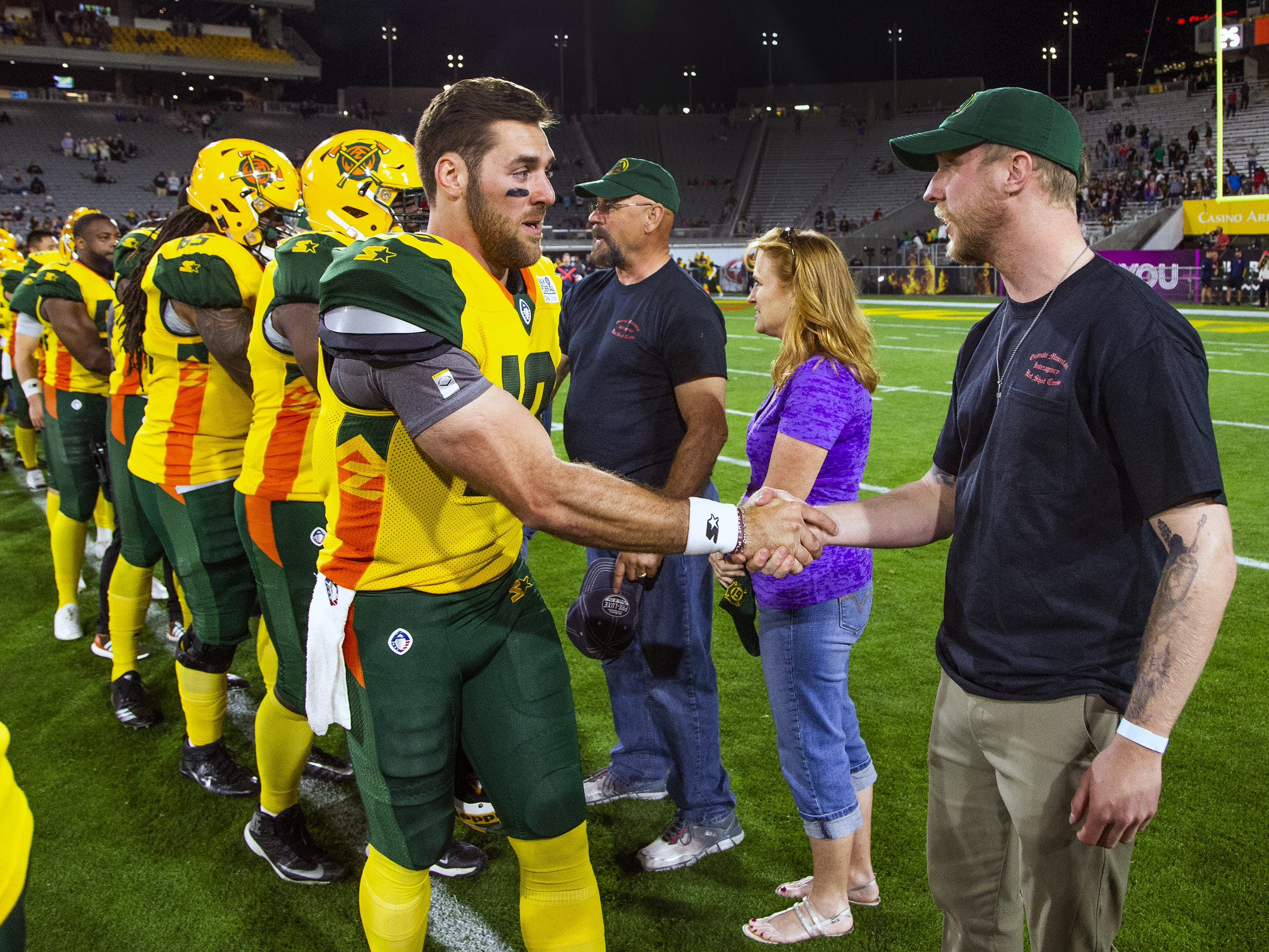 Brendan McDonough, the lone-surviving member of the Granite Mountain Hotshots, is greeted by quarterback Trevor Knight and other members of the Arizona Hotshots team after being honored along with family members of the crew at halftime of the Arizona Hotshots and Atlanta Legends football game at Sun Devil Stadium, Sunday, March 3, 2019.  A giant banner was unfurled, retiring the number 19 in honor of the fallen firefighters.