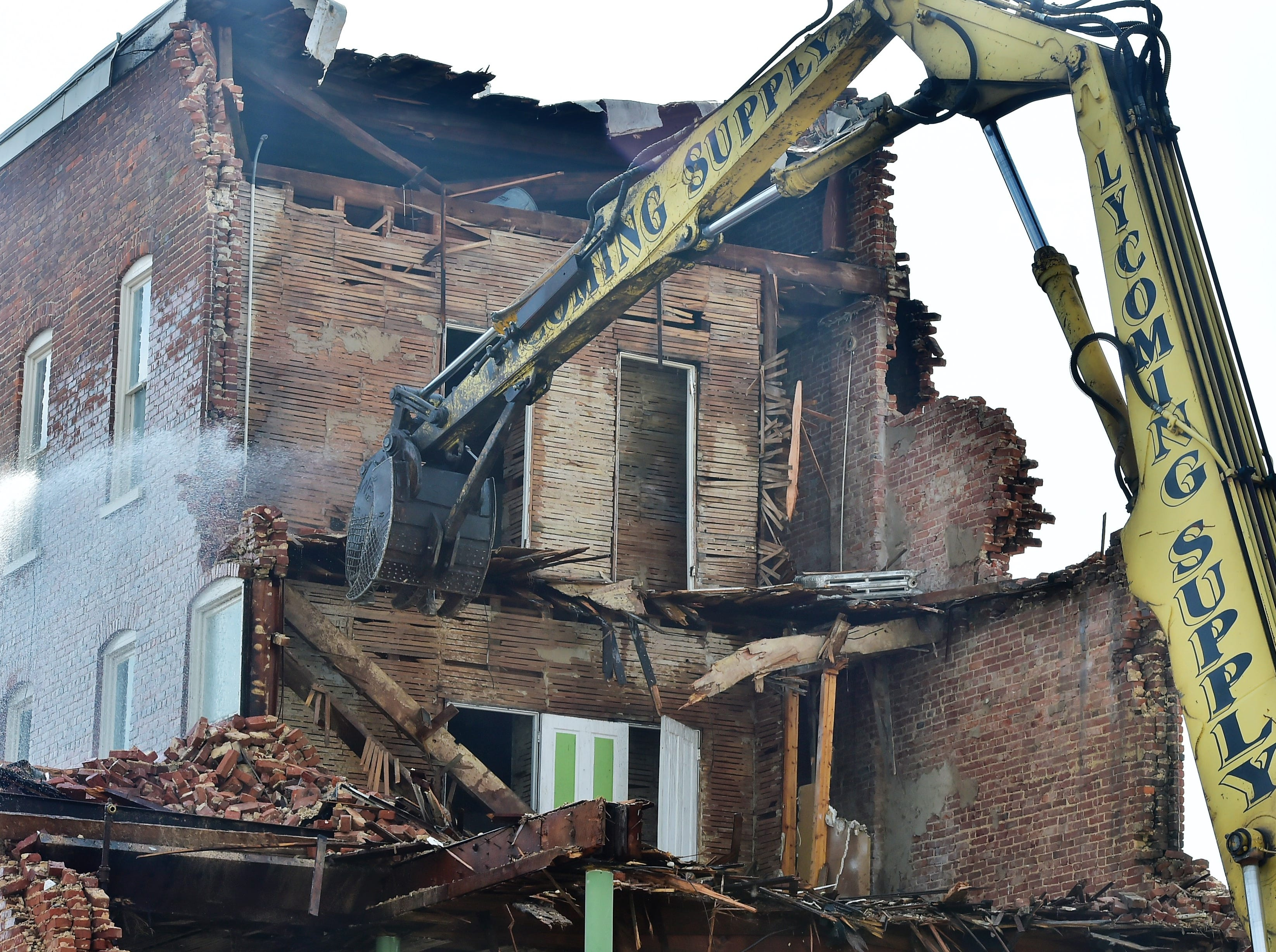 Water is sprayed to help settle dust as the old Wogan's Uniform building on North Main Street, Chambersburg, is demolished on Tuesday, April 9, 2019. Traffic will be limited to one lane through the end of the week as work continues. Lycoming Supply is tearing down structures in the first block of North Main Street as part of the $67.8 million Franklin County Court Facility Improvement Project. A judicial center will be built in the space.