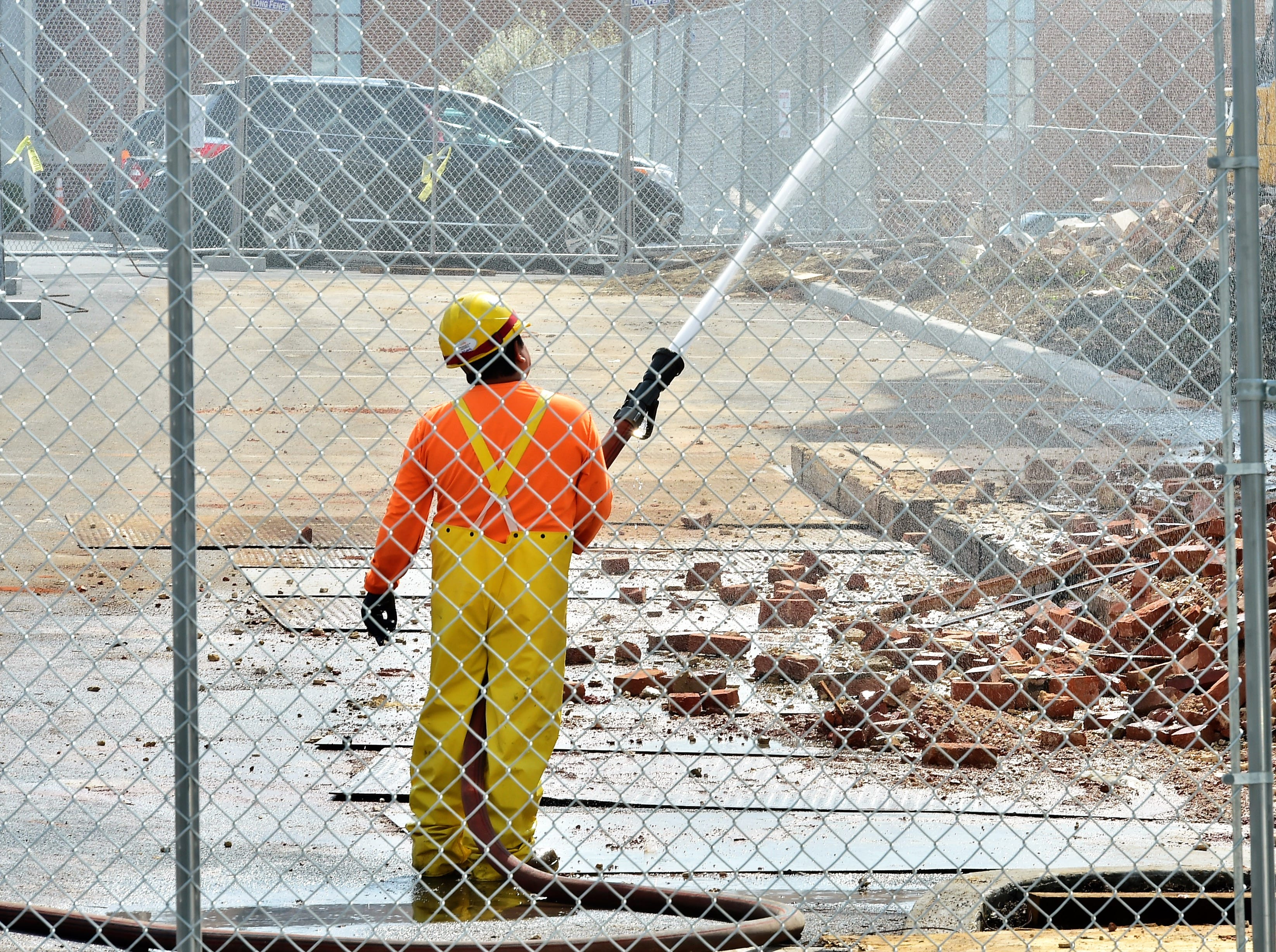 A man sprays water to settle flying dust as the old Wogan's Uniform building on North Main Street, Chambersburg, is demolished on Tuesday, April 9, 2019. Traffic will be limited to one lane through the end of the week as work continues. Lycoming Supply is tearing down structures in the first block of North Main Street as part of the $67.8 million Franklin County Court Facility Improvement Project. A judicial center will be built in the space.