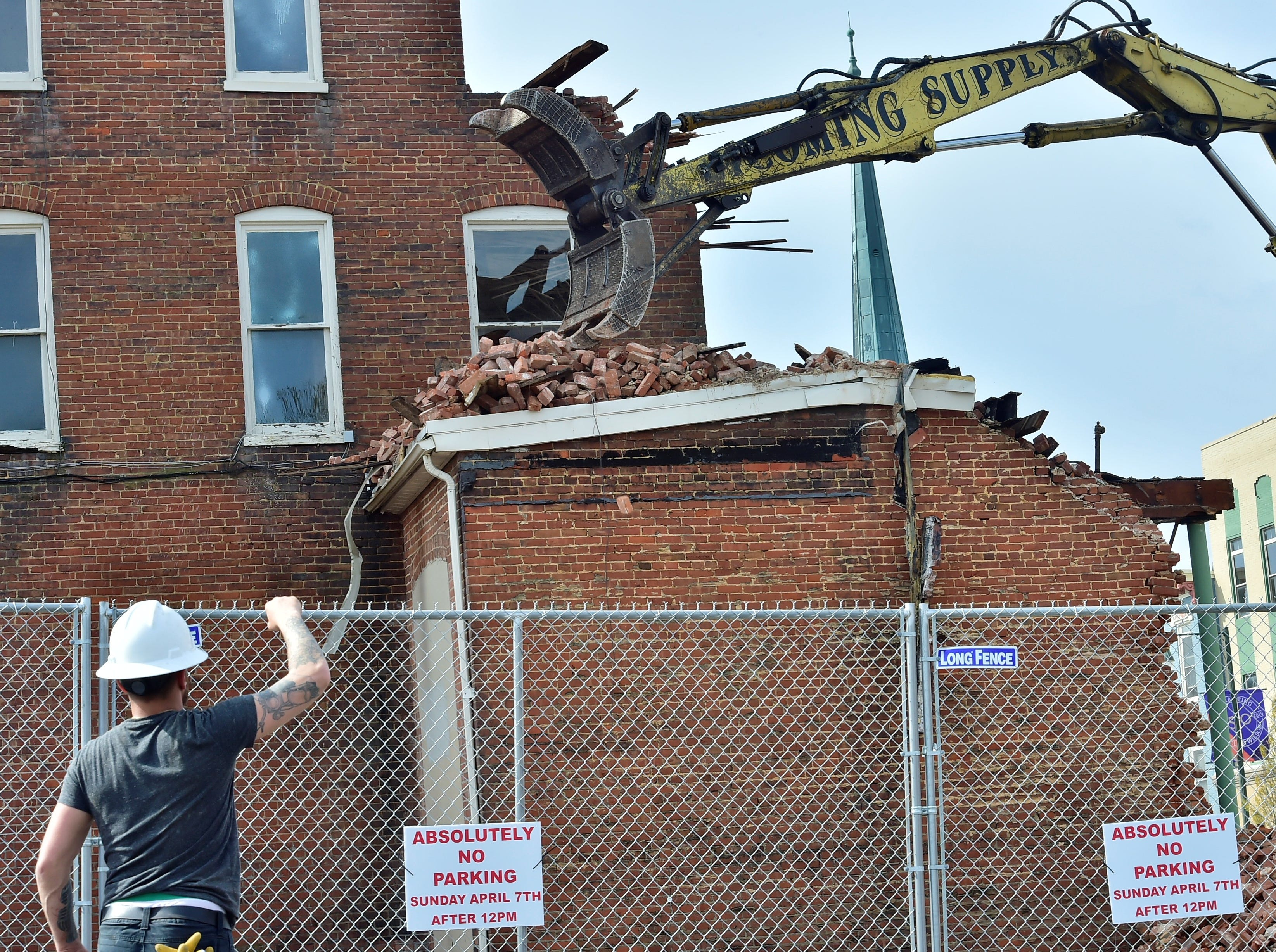 A man directs the operator of equipment being used to tear down the old Wogan's Uniform building on North Main Street, Chambersburg, on Tuesday, April 9, 2019. Traffic will be limited to one lane through the end of the week as work continues. Lycoming Supply is tearing down structures in the first block of North Main Street as part of the $67.8 million Franklin County Court Facility Improvement Project. A judicial center will be built in the space.