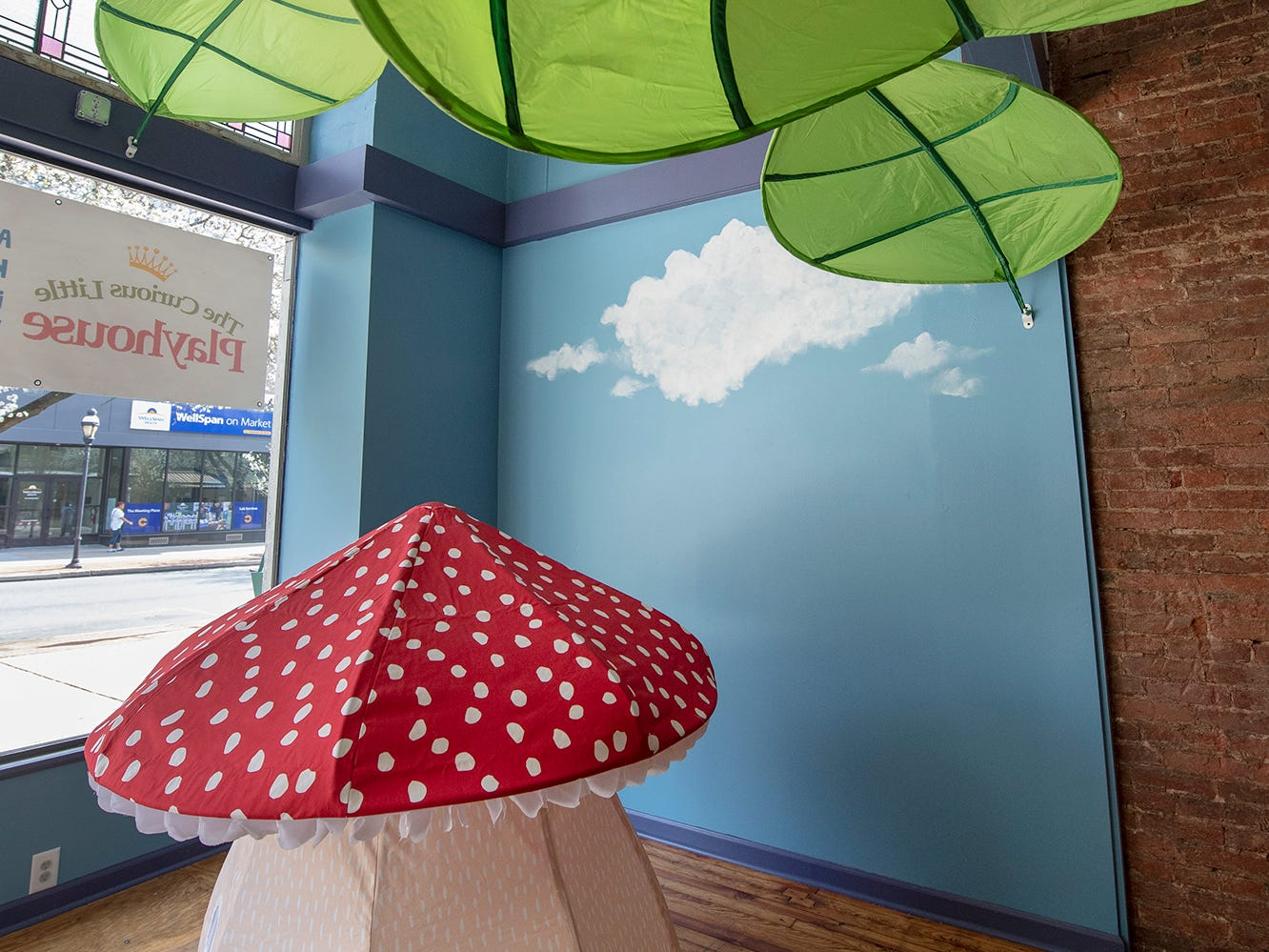 A mushroom playhouse and giant leaves decorate the display window of The Curious Little Playhouse, located at 41 West Market Street in York.