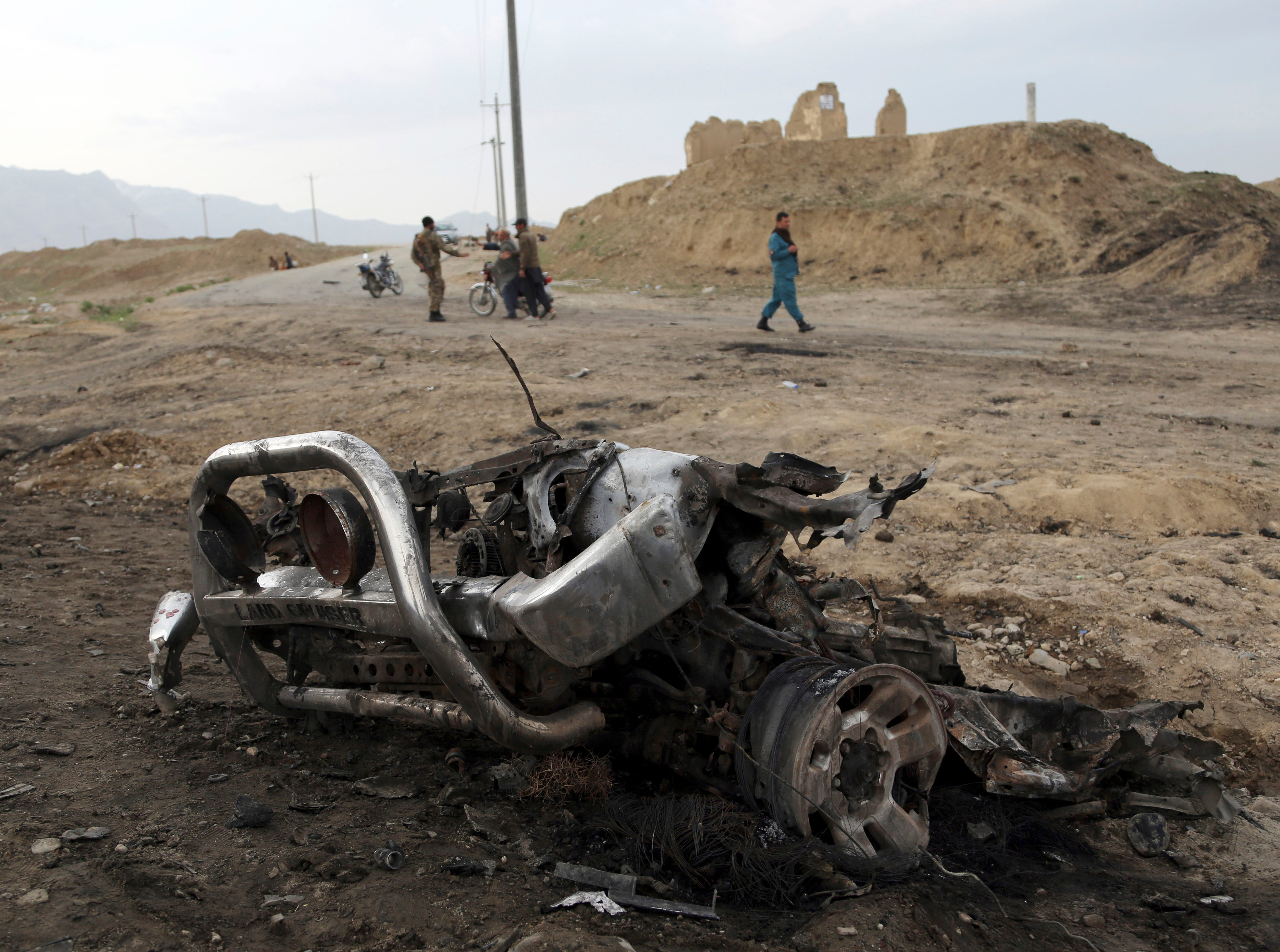 Afghan security forces gather at the site of Monday's suicide attack near the Bagram Air Base, north of Kabul, Afghanistan, Tuesday, April 9, 2019. Three American service members were killed when their convoy hit a roadside bomb on Monday near the main U.S. base in Afghanistan, the U.S. forces said. The Taliban claimed responsibility for the attack.
