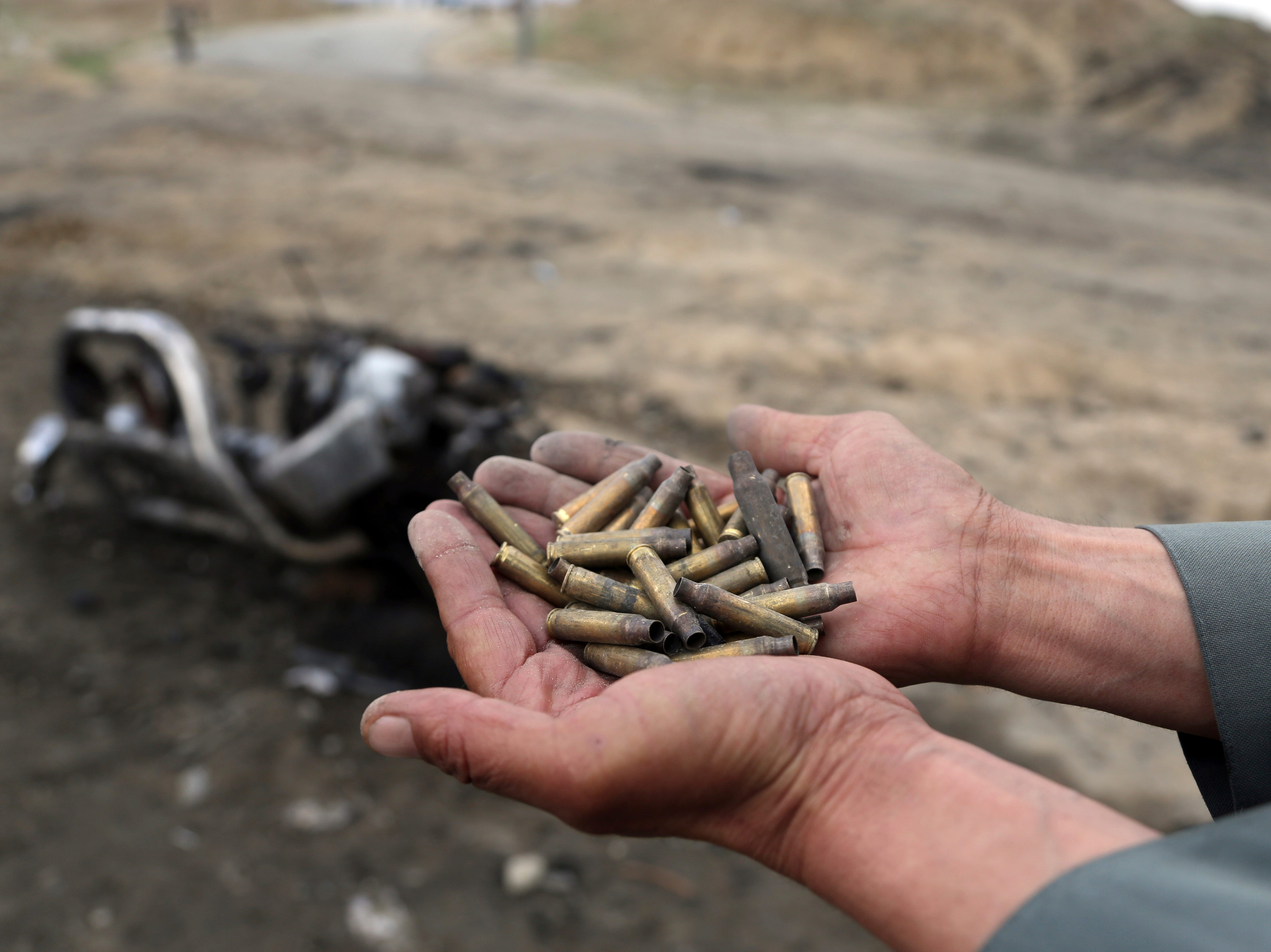 An Afghan security force hold bullet shell a day after an attack near the Bagram Air Base, north of Kabul, Afghanistan, Tuesday, April 9, 2019. Three American service members were killed when their convoy hit a roadside bomb on Monday near the main U.S. base in Afghanistan, the U.S. forces said. The Taliban claimed responsibility for the attack.