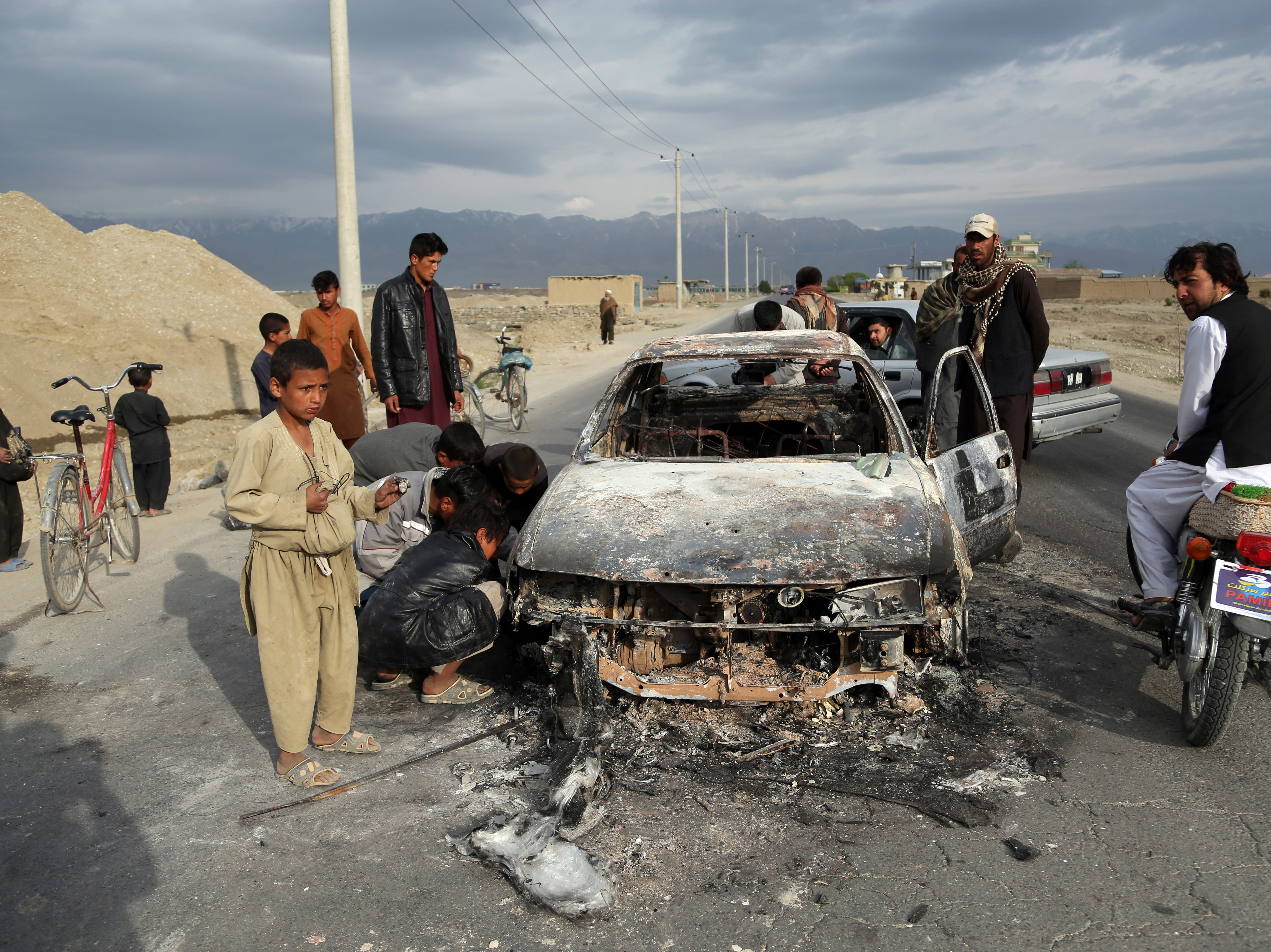 Afghans watch a civilian vehicle burnt after being shot by US forces after an attack near the Bagram Air Base, north of Kabul, Afghanistan, Tuesday, April 9, 2019. Three American service members  were killed when their convoy hit a roadside bomb on Monday near the main U.S. base in Afghanistan, the U.S. forces said. The Taliban claimed responsibility for the attack.