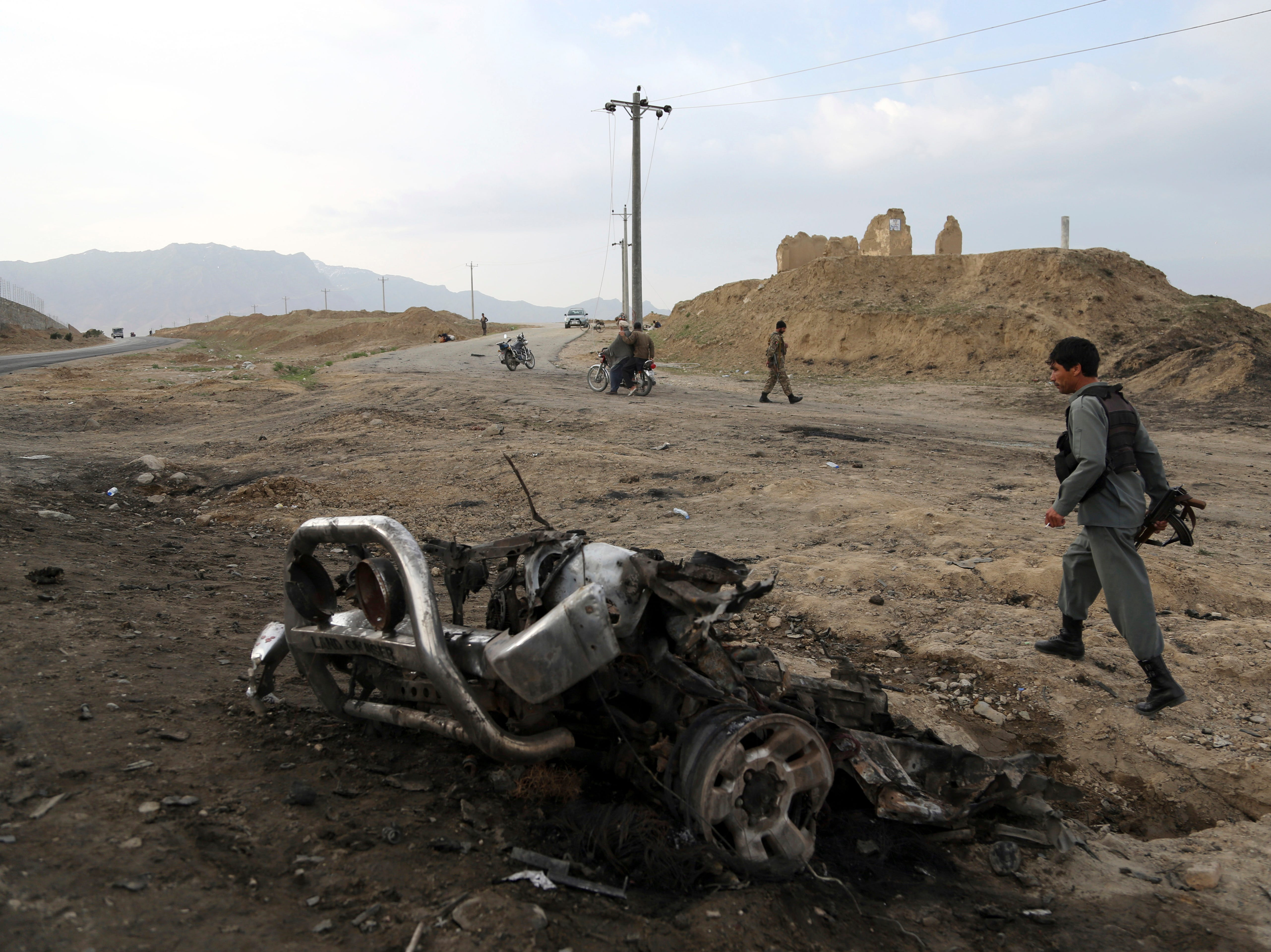 A member of Afghan security force walks at the site of Monday's suicide attack near the Bagram Air Base, north of Kabul, Afghanistan, Tuesday, April 9, 2019. Three American service members were killed when their convoy hit a roadside bomb on Monday near the main U.S. base in Afghanistan, the U.S. forces said. The Taliban claimed responsibility for the attack.