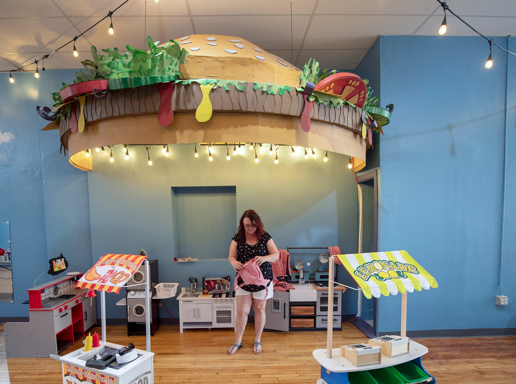 Jen Swanner folds an apron at the Diner and interactive play station at The Curious Little Playhouse.
