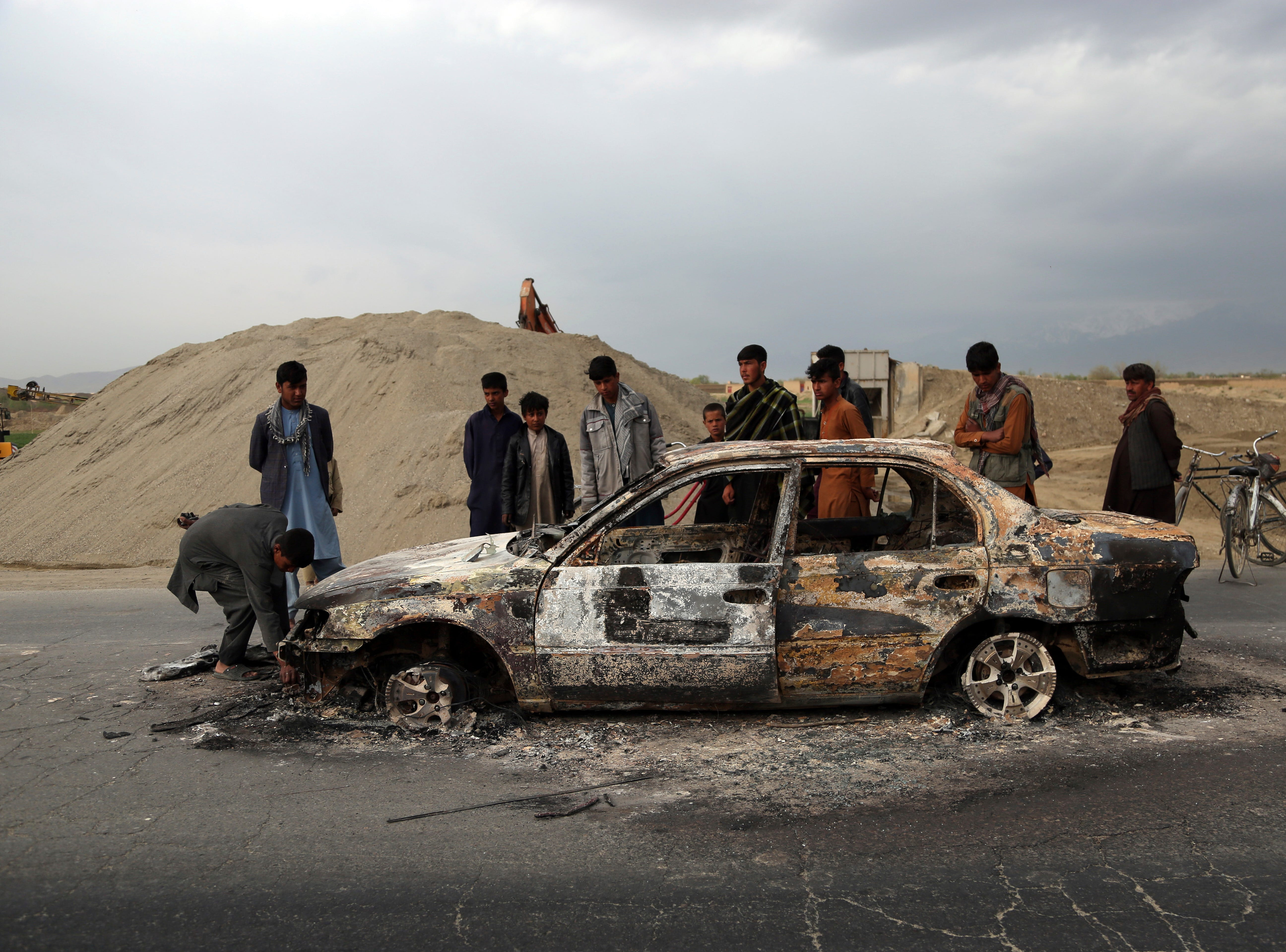 Afghans watch a civilian vehicle burnt after being shot by US forces following an attack near the Bagram Air Base, north of Kabul, Afghanistan, Tuesday, April 9, 2019. Three American service members were killed when their convoy hit a roadside bomb on Monday near the main U.S. base in Afghanistan, the U.S. forces said. The Taliban claimed responsibility for the attack.