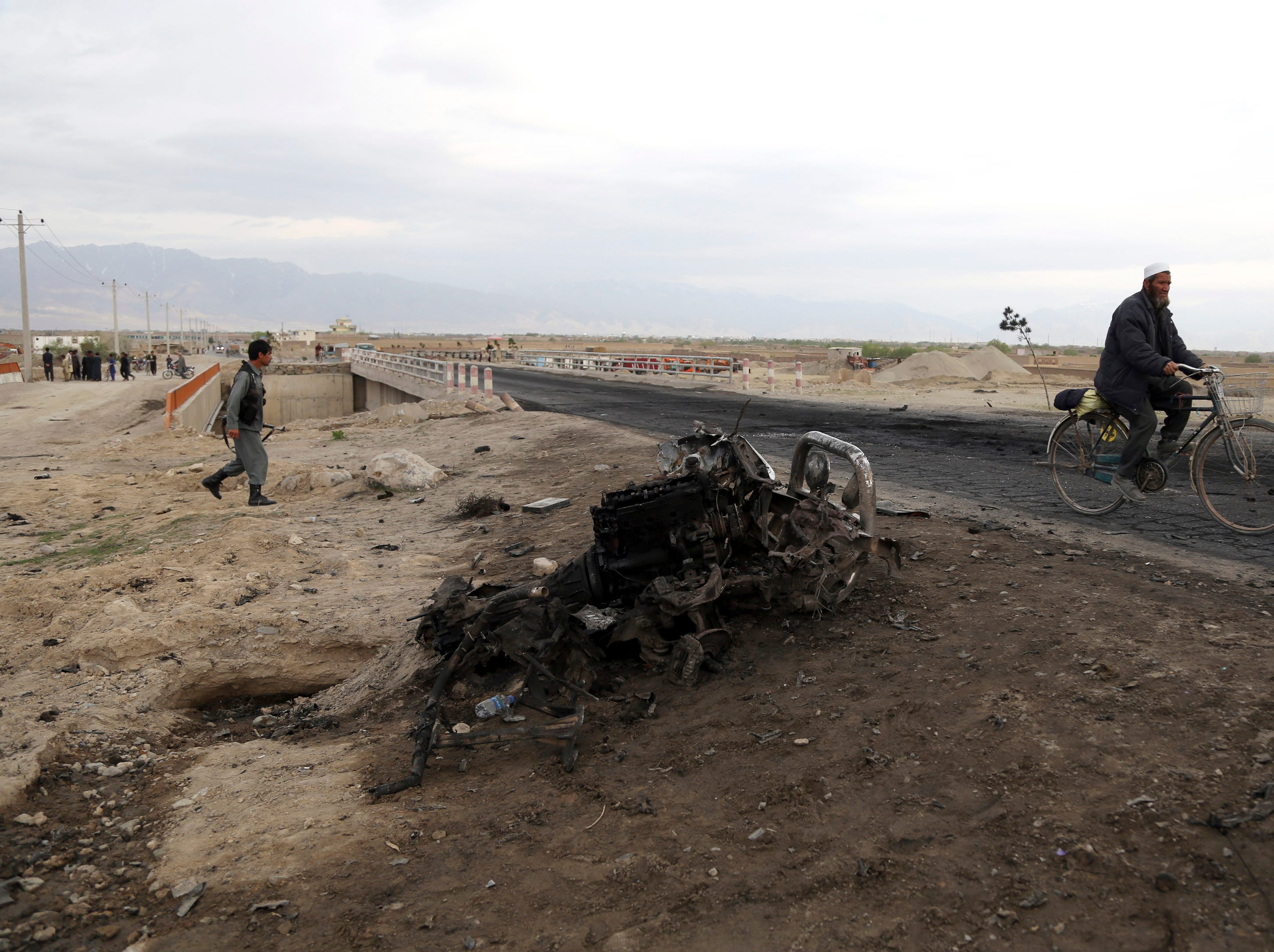 A man cycles past the site of Monday's suicide attack near the Bagram Air Base, north of Kabul, Afghanistan, Tuesday, April 9, 2019. Three American service members were killed when their convoy hit a roadside bomb on Monday near the main U.S. base in Afghanistan, the U.S. forces said. The Taliban claimed responsibility for the attack.